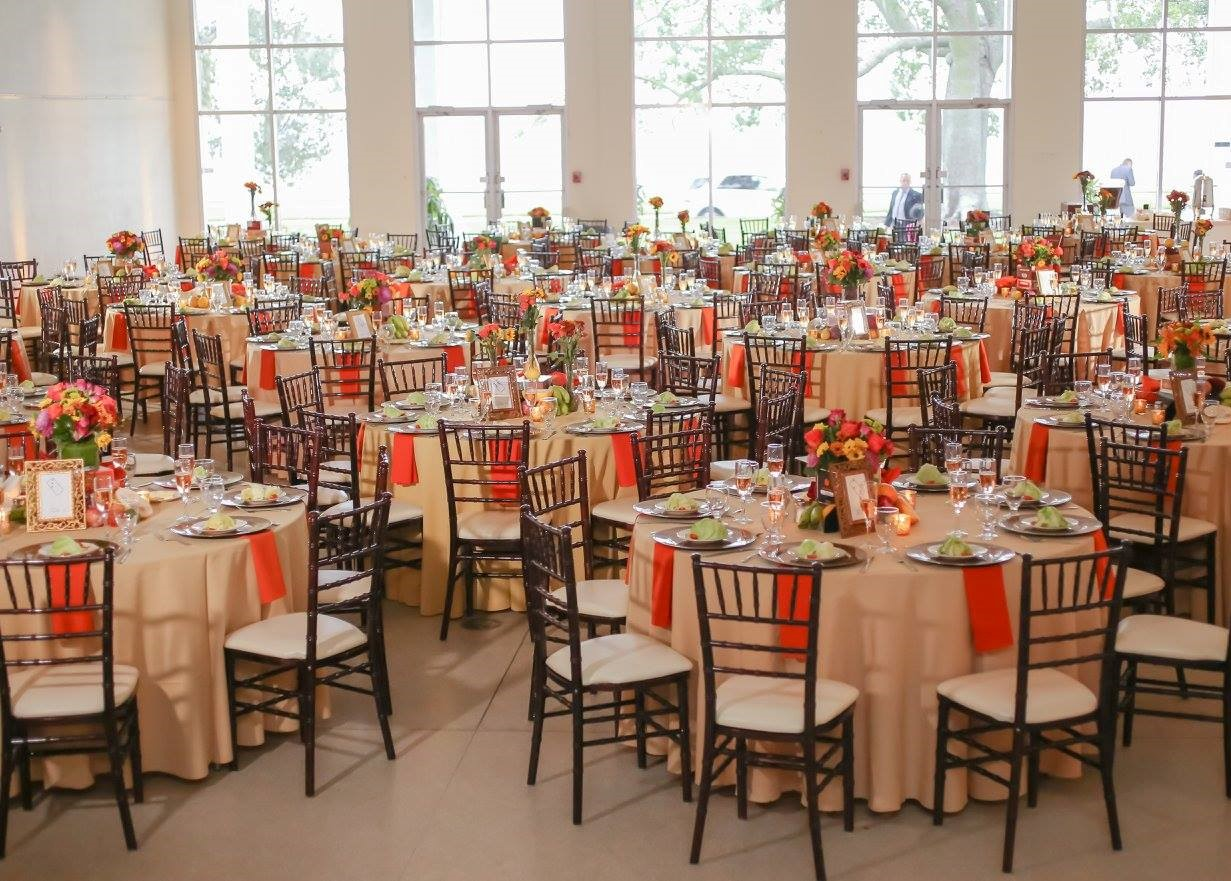 Mahogany Chiavari chairs and tropical colored linens were adorned with candle light and table numbers in gold frames, helping to marry the harvest and Havana themes!