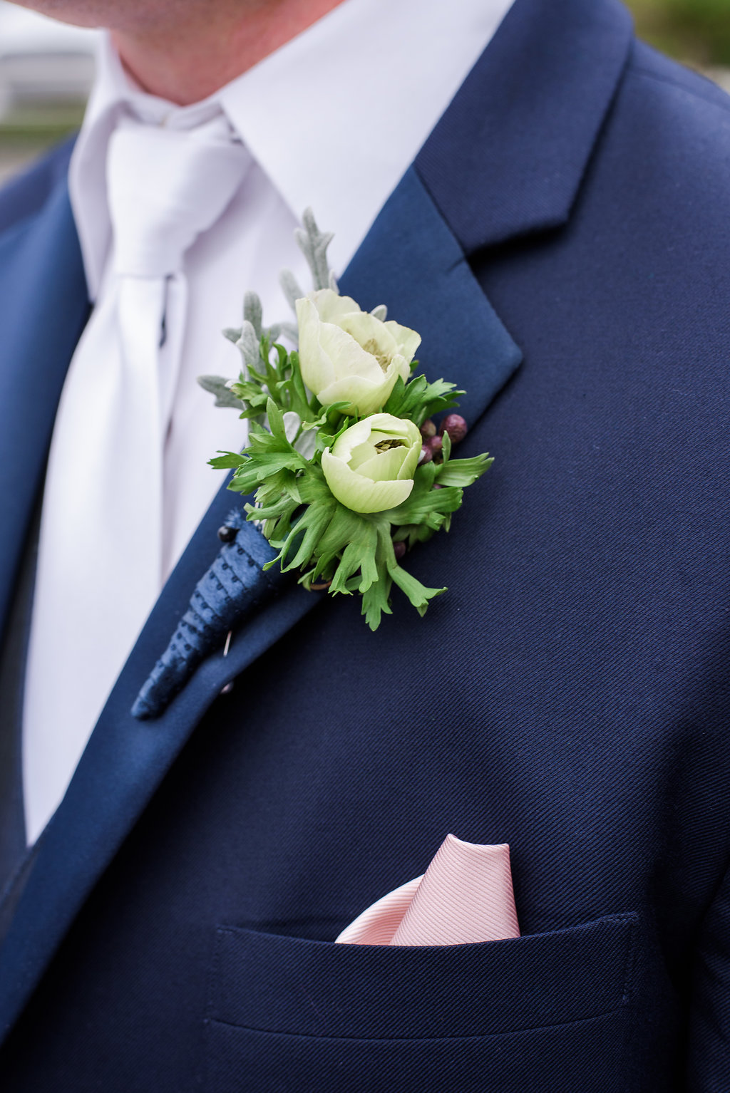 Greenery and neutral florals accented the groom's navy suit.