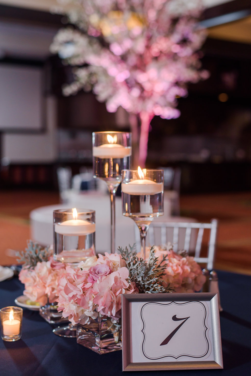 Tables were dressed in sleek linens and aglow with candlelight accenting soft floral centerpieces.