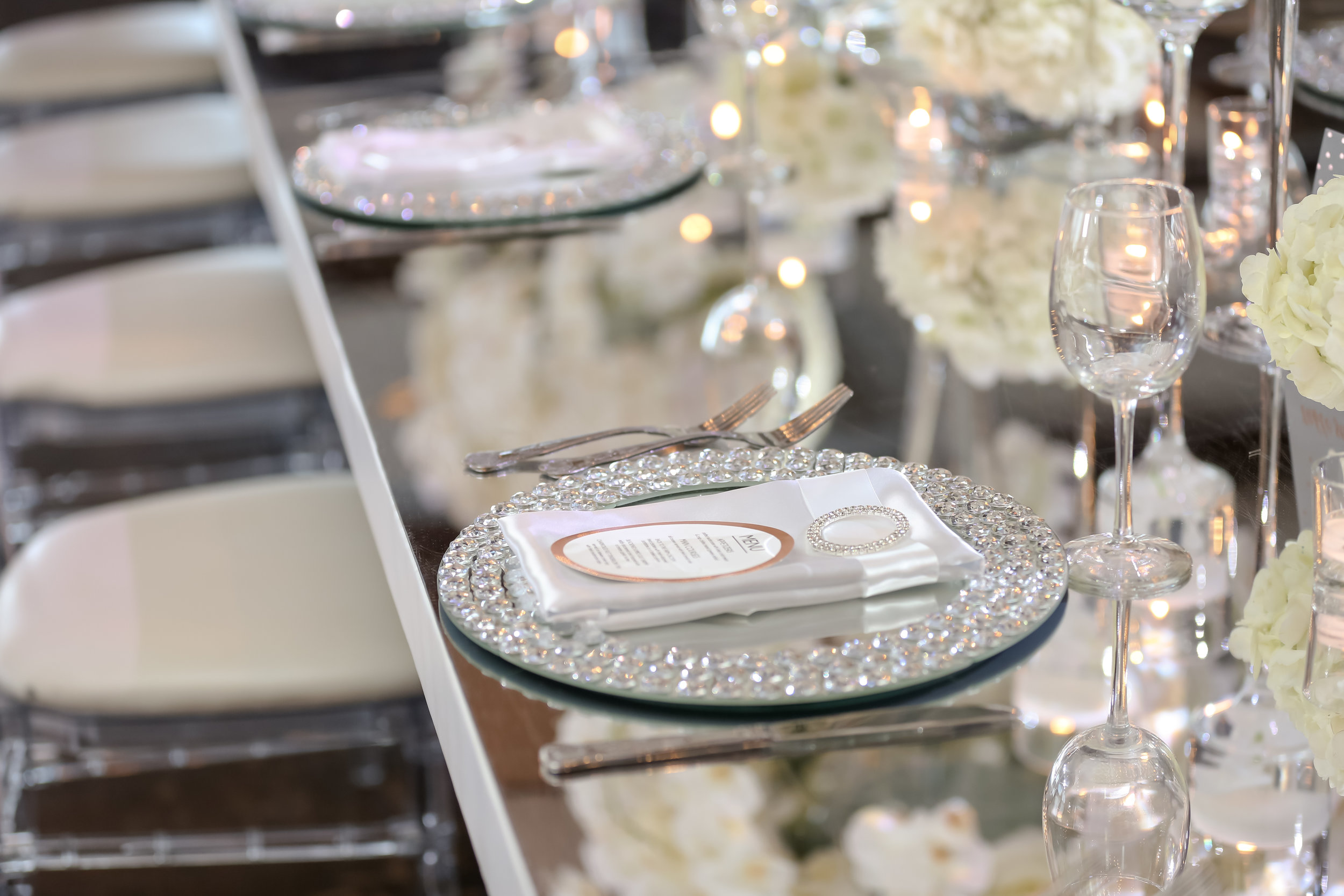 Feasting tables featured mirror tops, and place settings were accented with rhinestone napkin rings.