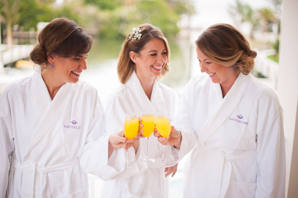 The bride and bridesmaids enjoy mimosas while wrapped in fluffy hotel robes.