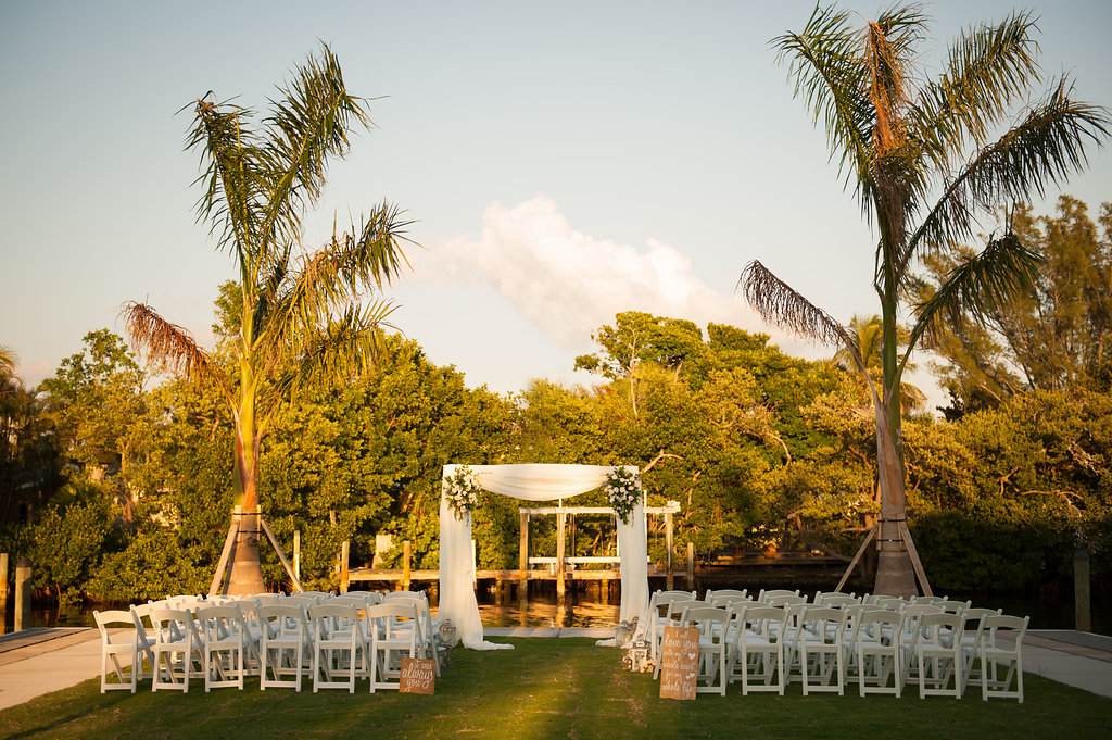 A seaside ceremony between palm trees, took place in front of a chiffon draped arch with complimentary floral arrangements.