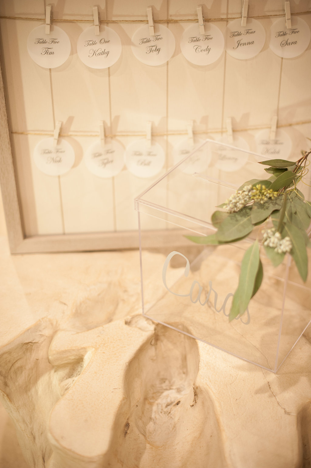 Escort cards, that were made to resemble mother-of-pearl shells, were displayed above a driftwood table.