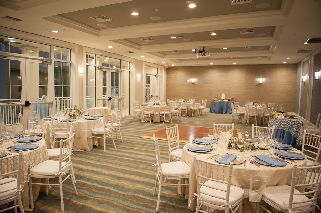White linens with sheer overlays in varying textures and patterns, were paired with pops of blue and silver in the ballroom.