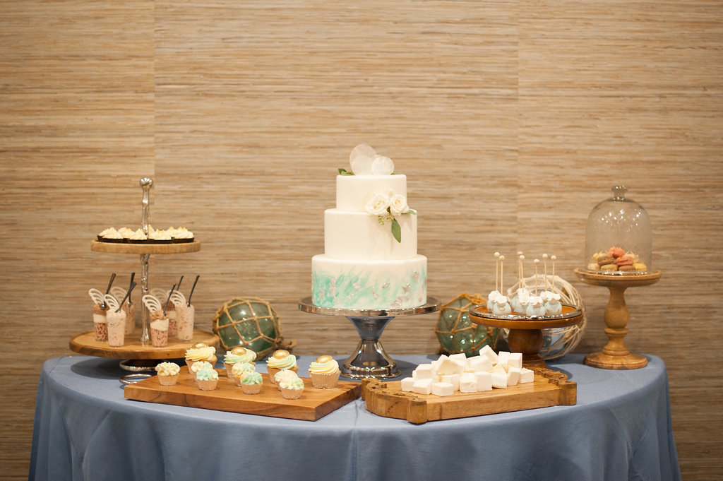 A dessert display boasted a coastal-inspired three tiered cake, cupcakes, cake pops, macarons, and handmade marshmallows, accented with nautical displays like wood trays, rope, and seaglass.