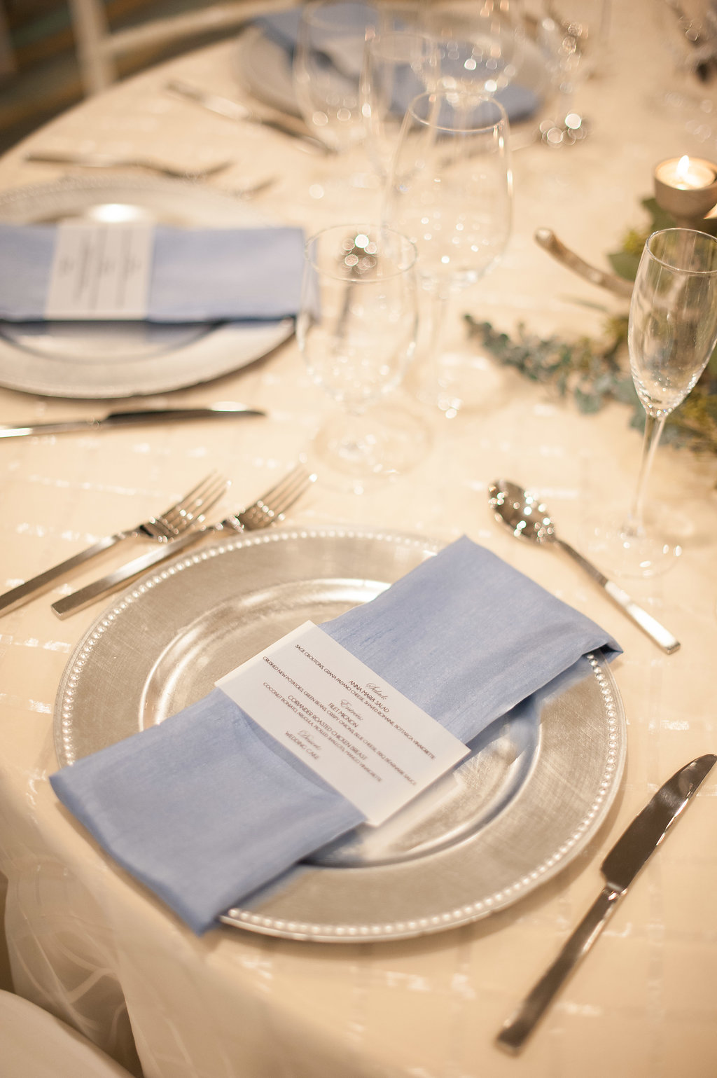 The silver chargers set with blue napkins, and elegant script menus brought a hint of watercolor to the neutral tables.