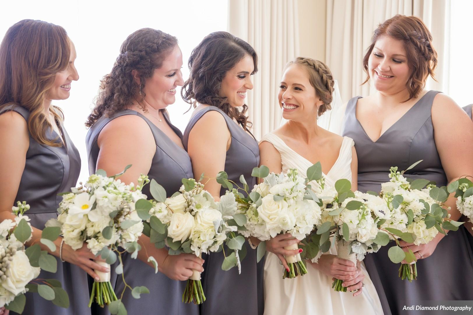 To keep things simple and sophisticated the bride chose matching bouquets of ivory florals with greenery to subtly pop against the bridesmaids' charcoal dresses.