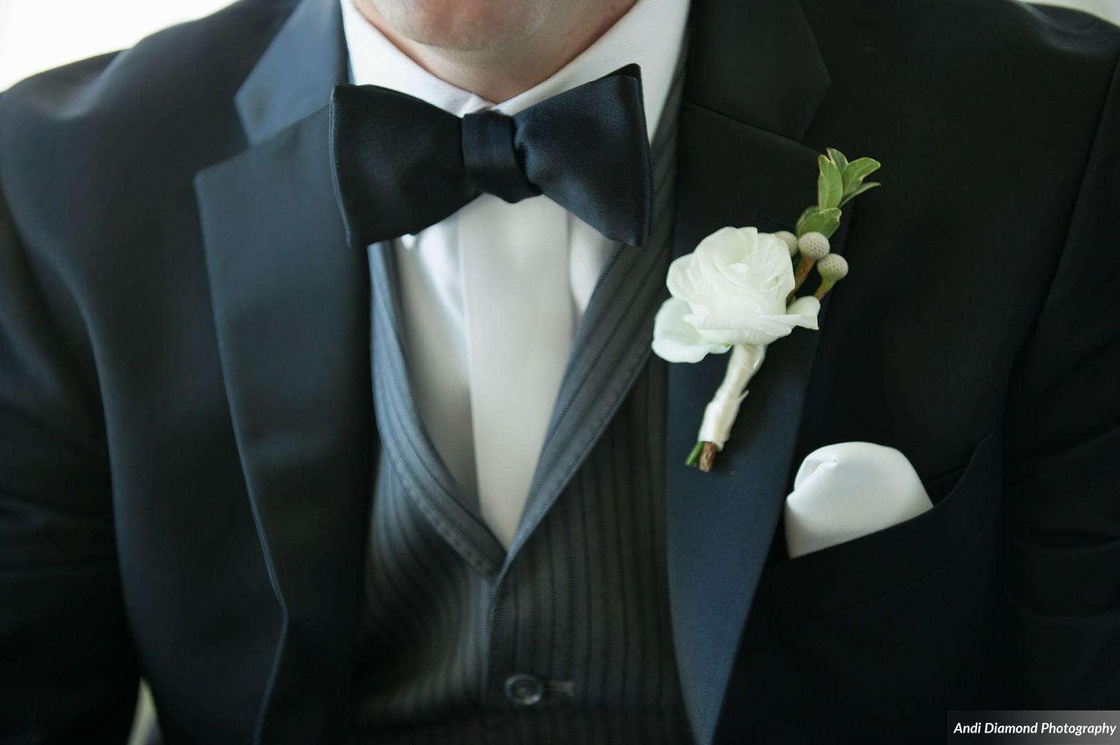 The groom wore a sharp three piece suit in complimenting shades of charcoal with pops of ivory details.