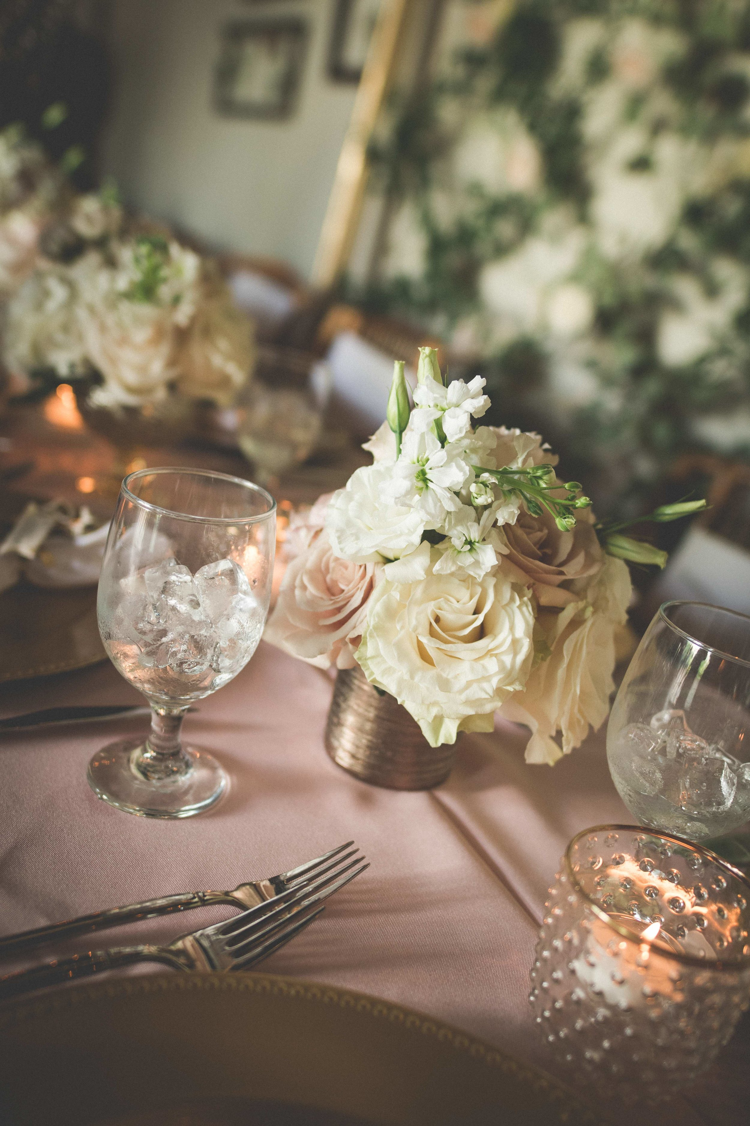 Gold and rose gold details were displayed amongst blush linens, soft candlelight, and bouquets of ivory and blush florals.