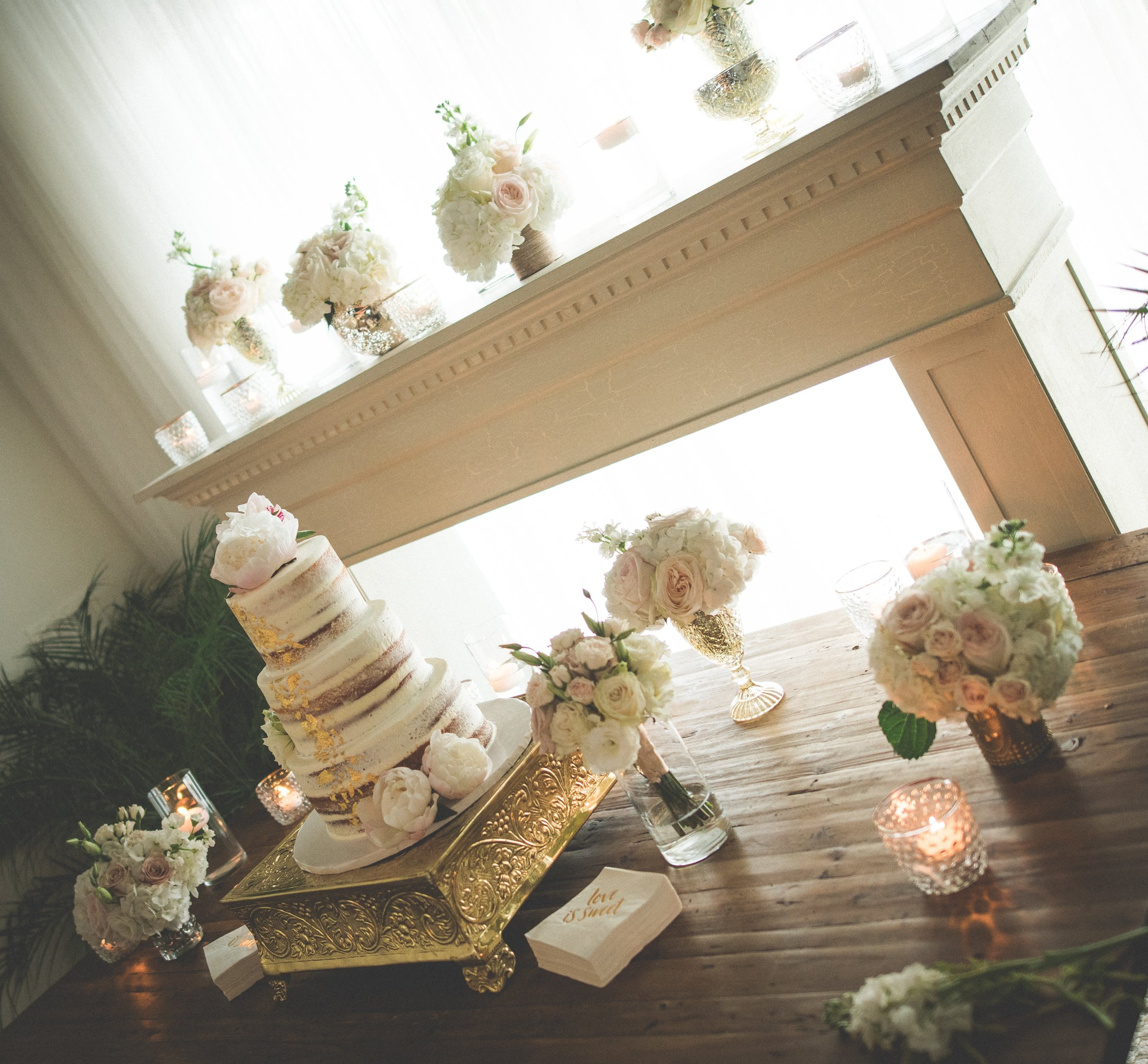A handmade mantle was used as a focal point and backdrop for the simple and sophisticated three tiered cake, which was decorated with metallic gold accents and fresh peonies.