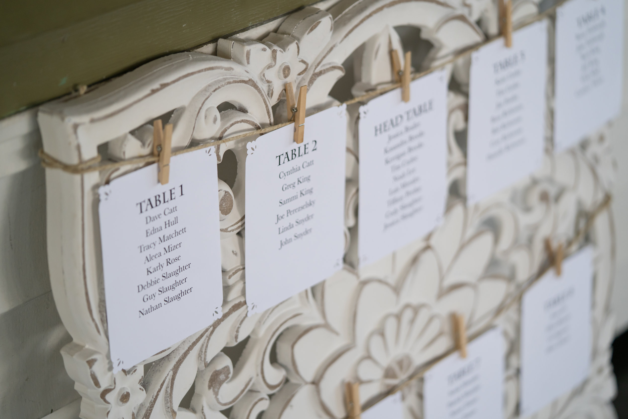 Delicate laser cut seating chart cards were hung by miniature clothes pins against a carved wood backdrop.