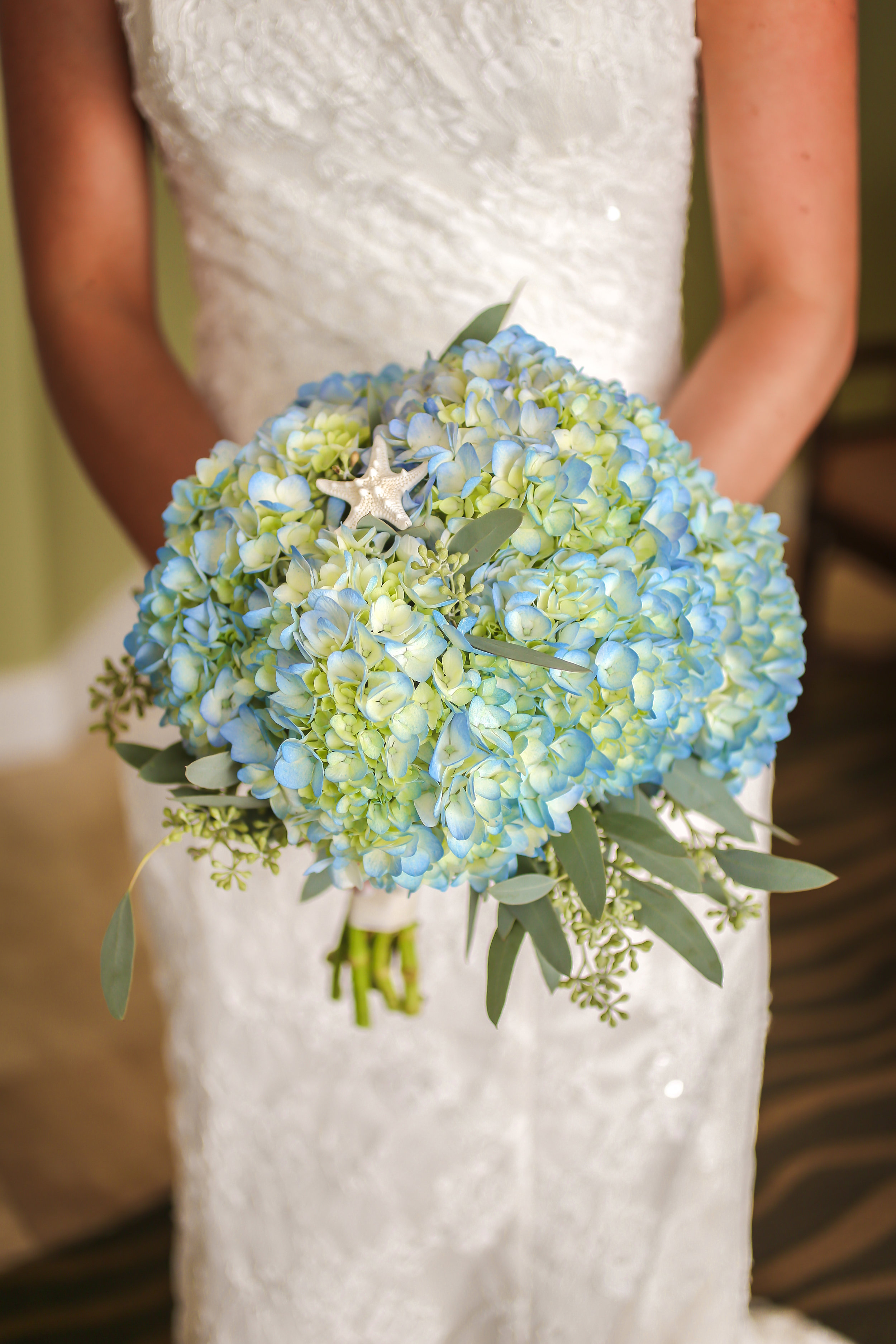 The bride carried a bouquet of blue, green, and white hydrangea accented with greenery and starfish elements.