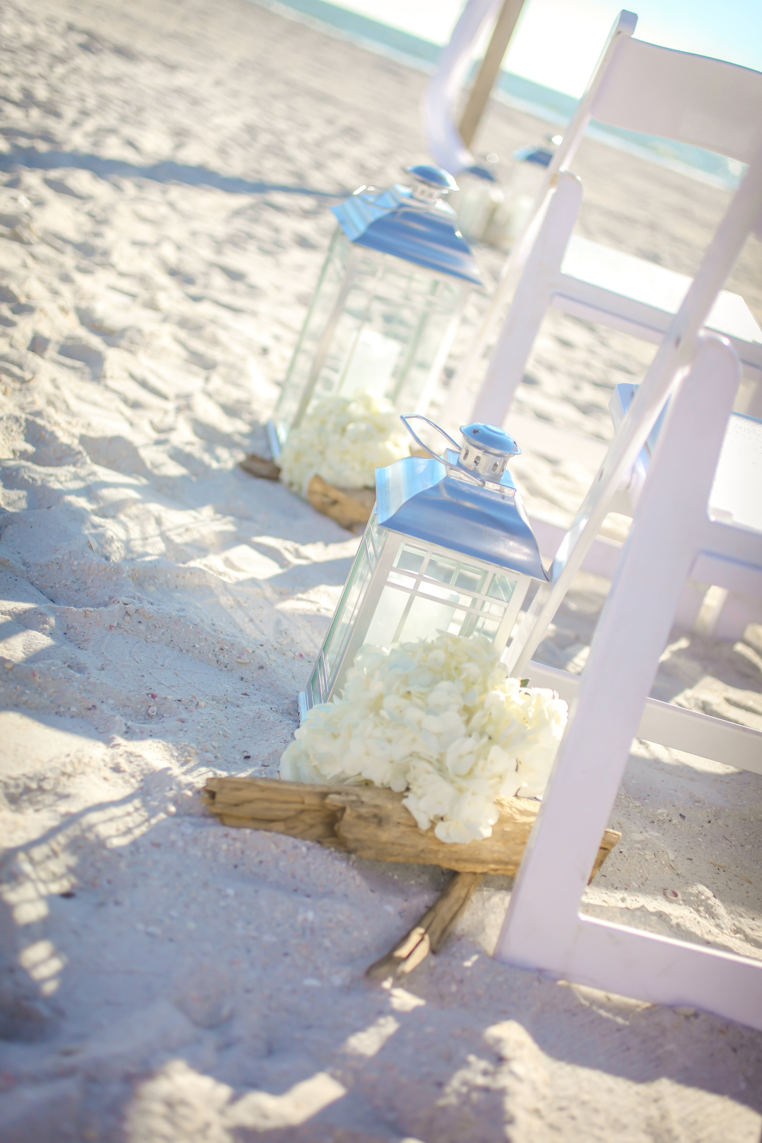 Along the ceremony aisle, lanterns and driftwood sat beside guest chairs.