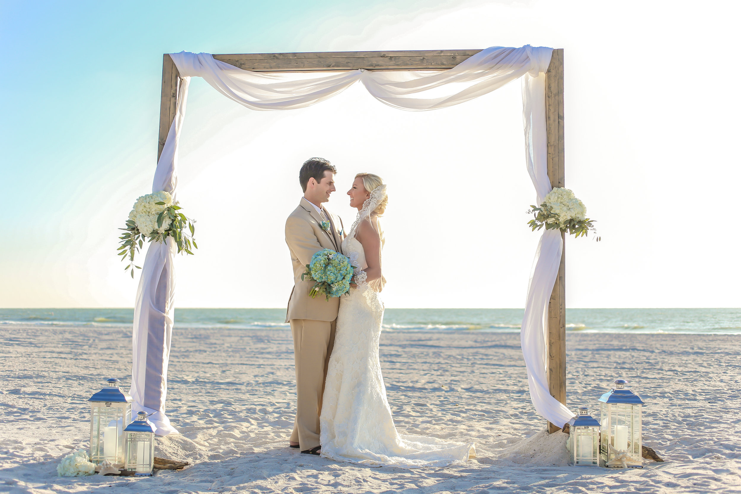 The couple were married beneath a natural wood ceremony arch adorned with neutral flowers, lanterns, and chiffon drapery.
