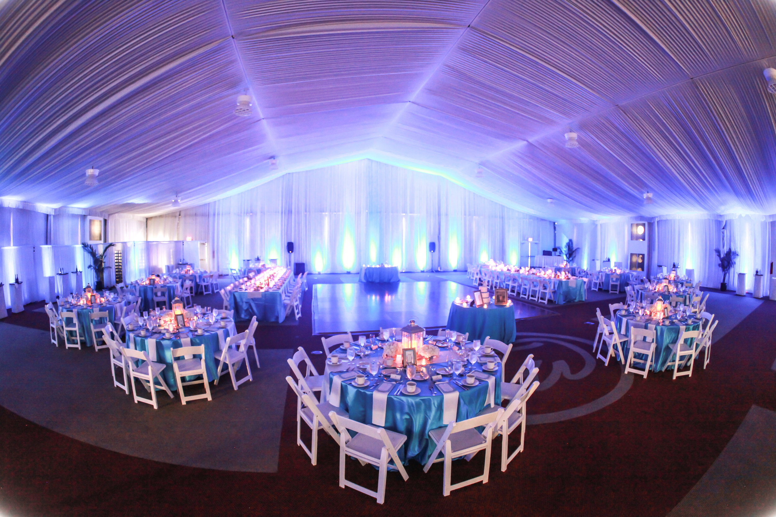 The reception was held in the event pavilion, fully draped with chiffon drapery from the ceiling and along the walls and completed with uplighting throughout in blue hues.