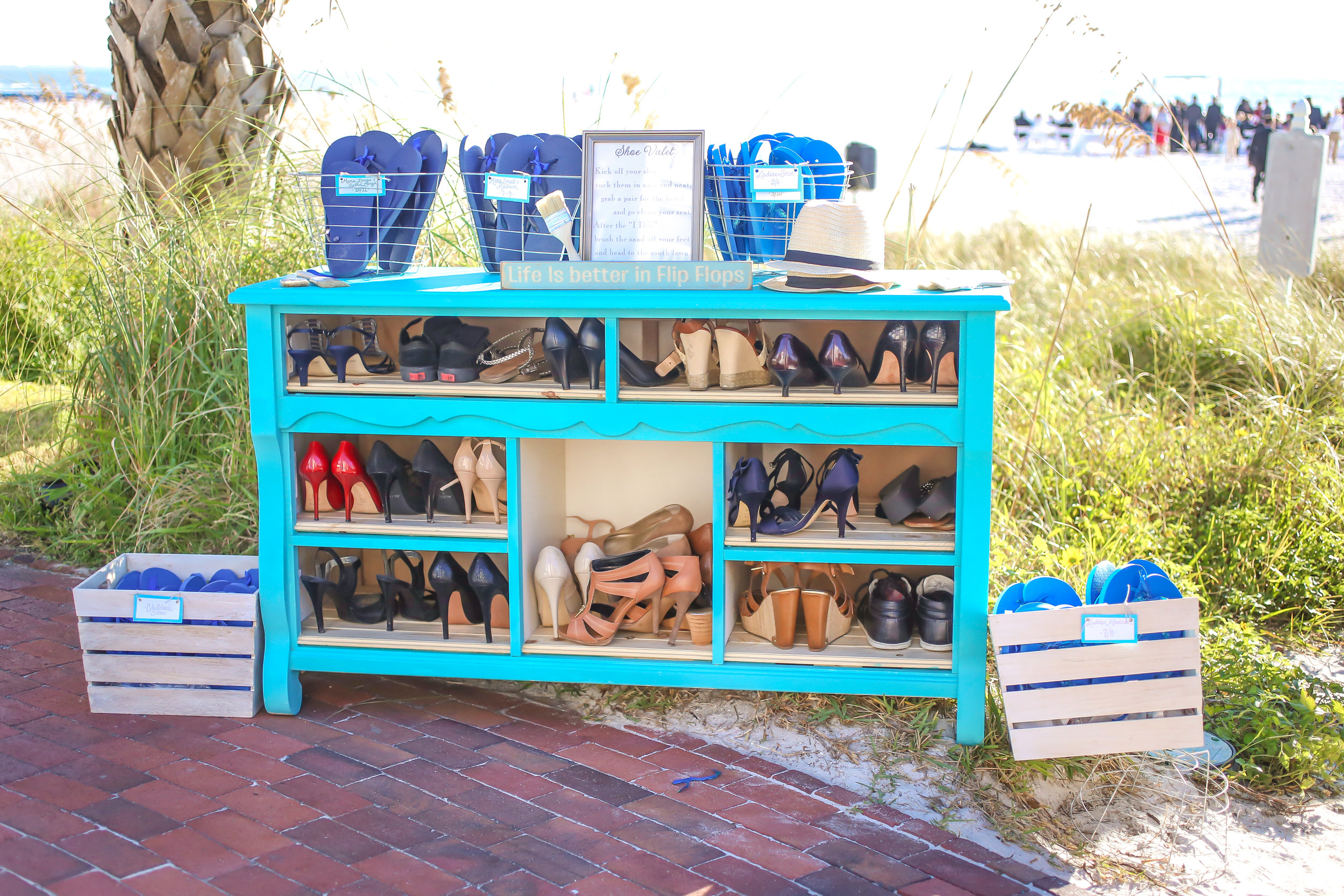 "A vintage dresser was converted into a ""shoe valet"" for guests to kick off their shoes and grab a pair of flip flops for the beachfront ceremony."