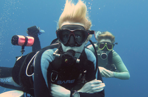 2 TDI sdiemount scuba divers are females looking at the camera. They are performing a safety stop while waiting for coconut tree divers boat to pick them up.