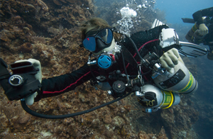 a TDI / PADI technical sidemount scuba diver is performing a NOTOX gas switch underwater. There is another diver behind her from coconut tree divers, he is checking to make sure the gas switch is correct.