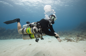 an Xdeep sidemount diver with the tec center in roatan is being photographed by a diver from coconut tree divers on a sandpatch in the caribbean waters.