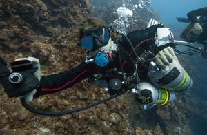 a sidemount technical diver holding out her dive rite second stage regulator. One of coconut tree divers are behind her diving along side the wall in roatan.