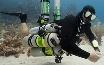 technical sidemount diver ready for a trimix dive with coconut tree divers in roatan, he is hovering above the sandpatch with 9 tanks attached to him.
