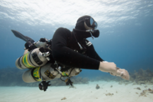 techncial sidemount scuba diver on a sandpatch diving off of coconut tree divers boat in roatan.