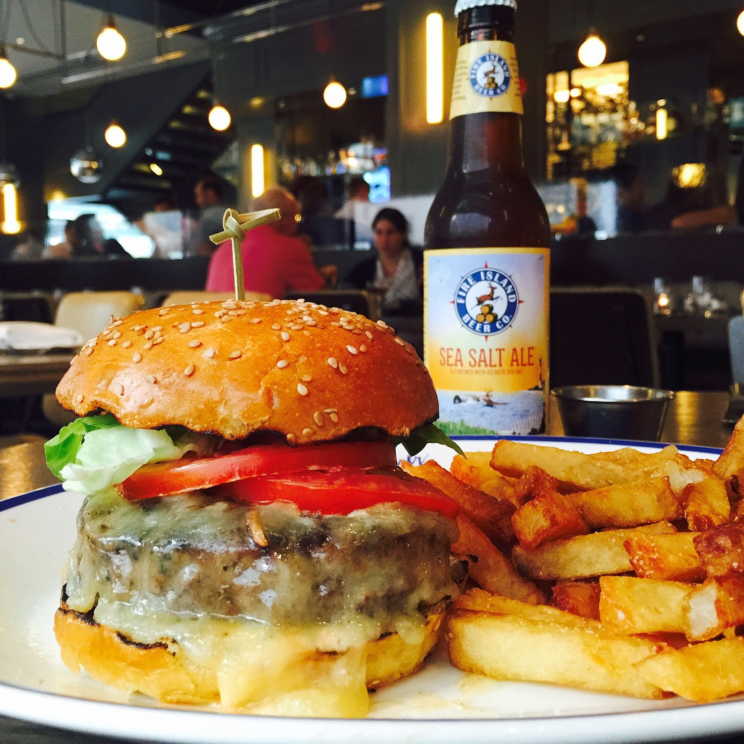 plate with cheeseburger and french fries with a beer