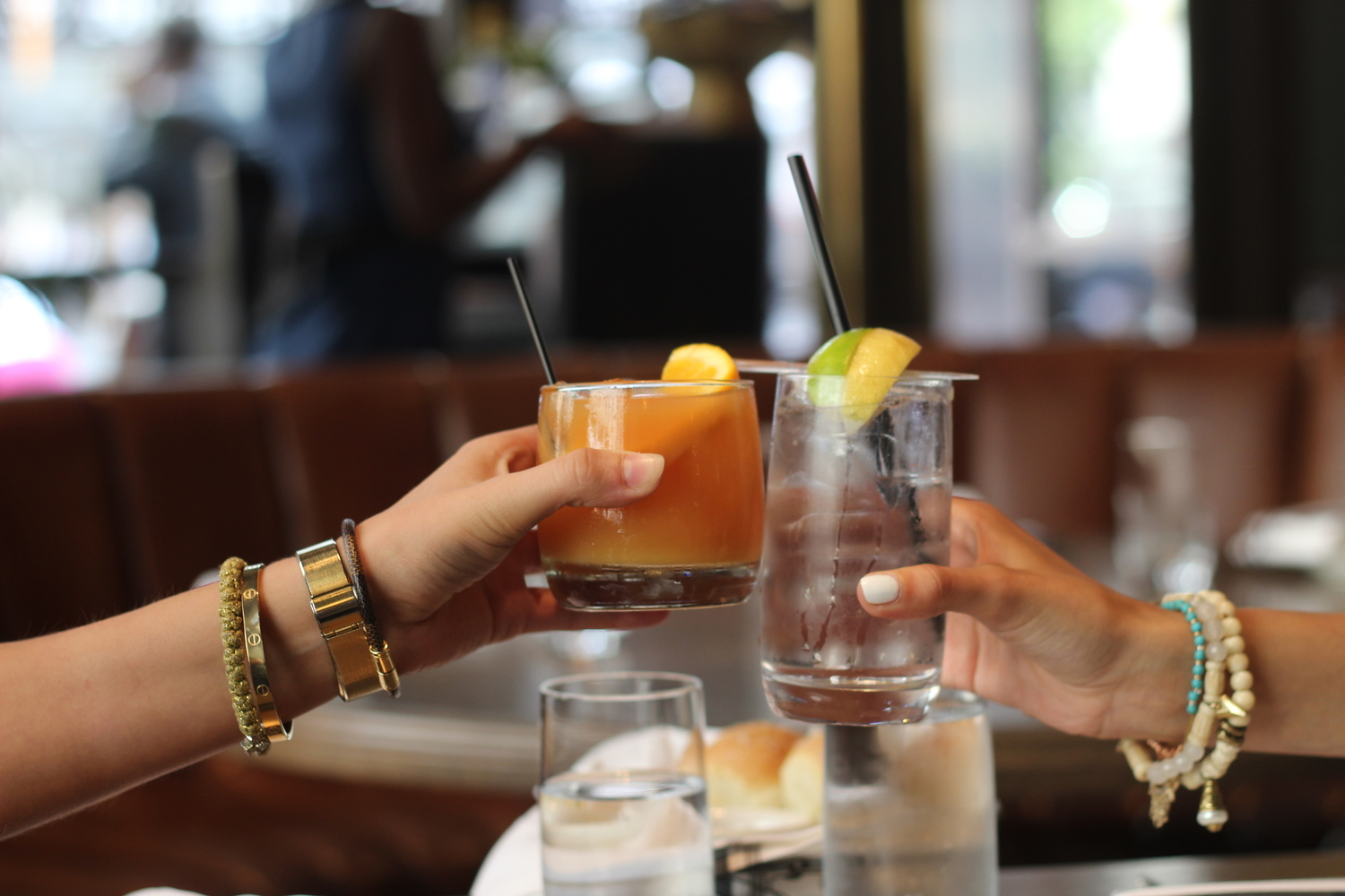 two people cheersing cocktails