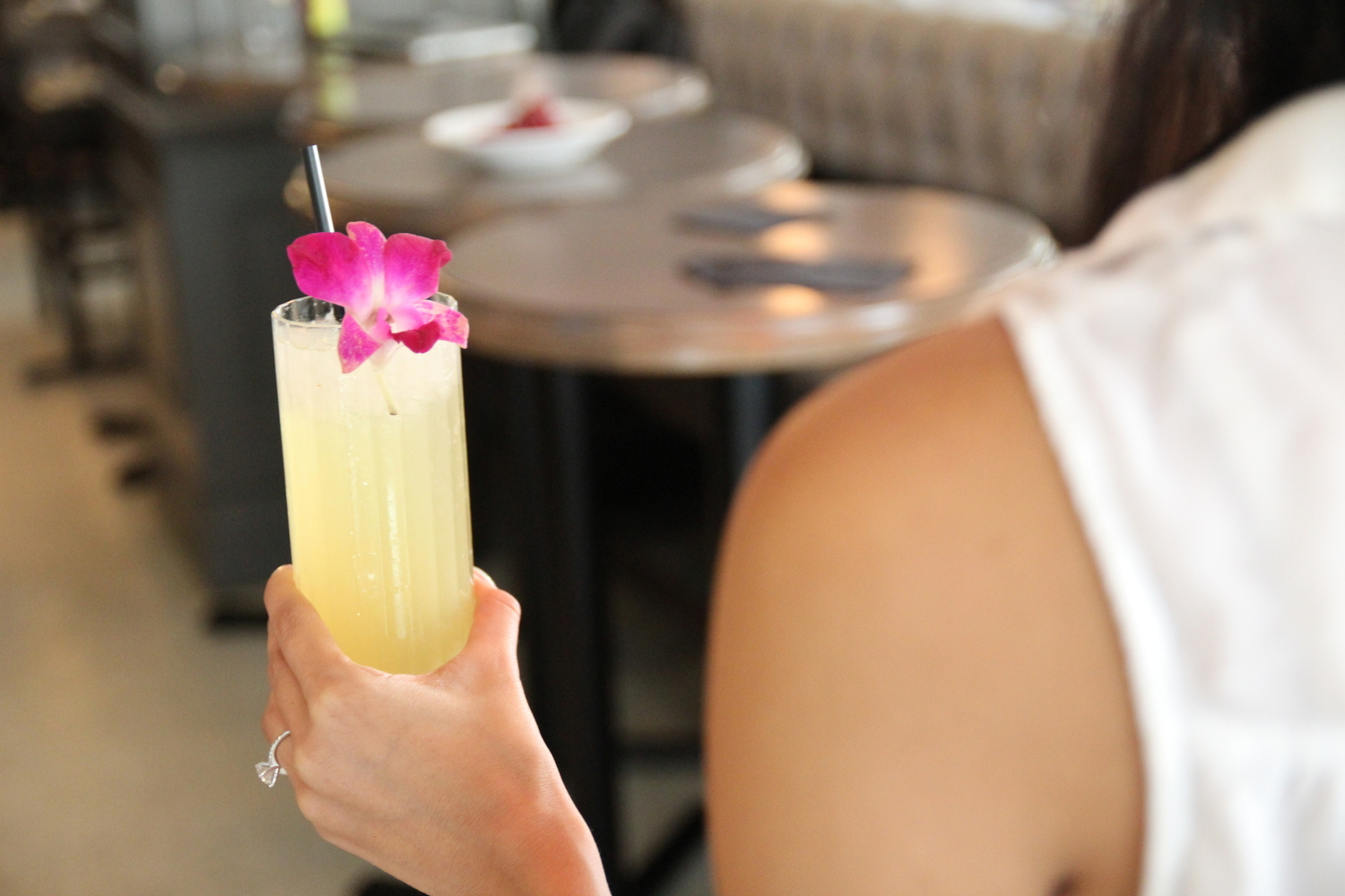 bride to be holding cocktail with orchid