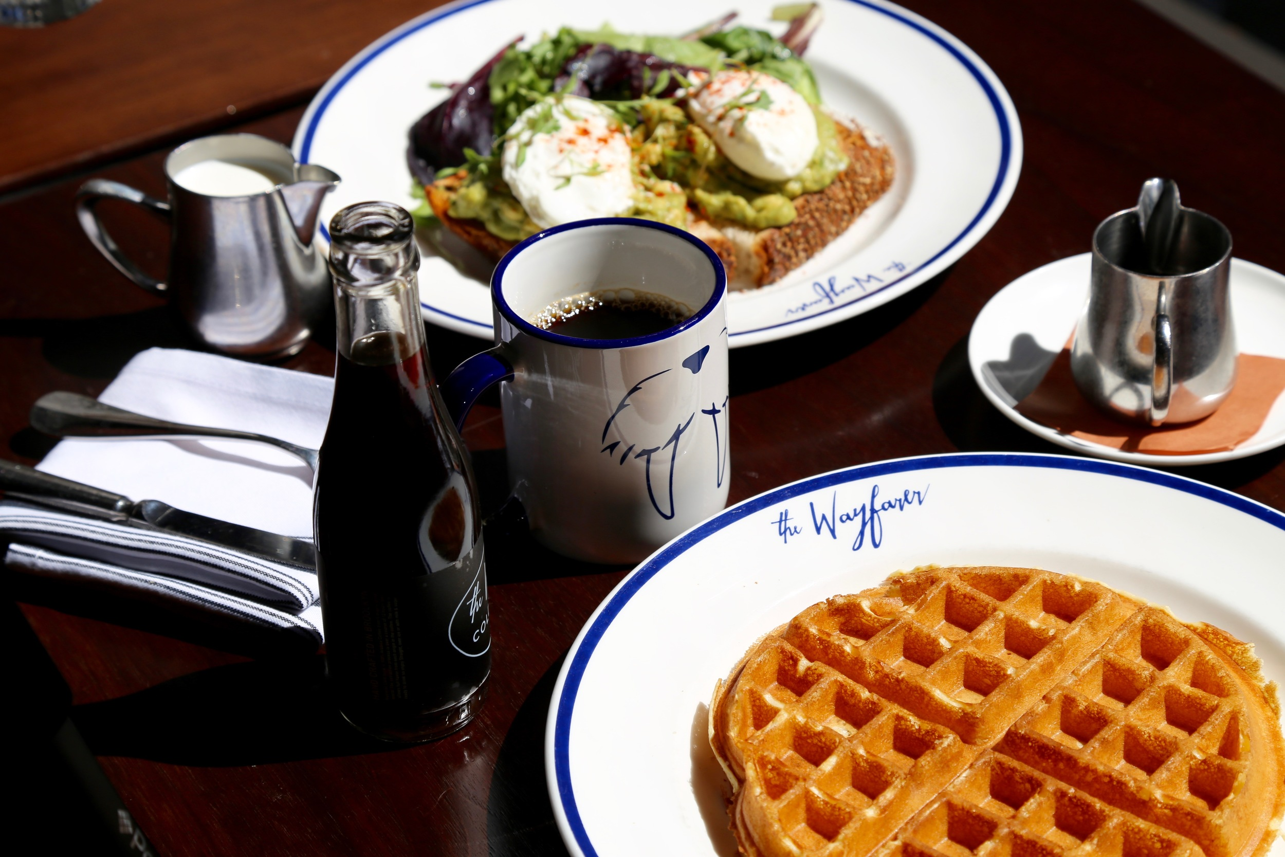 different angle of table with coffee, waffle and avocado toast