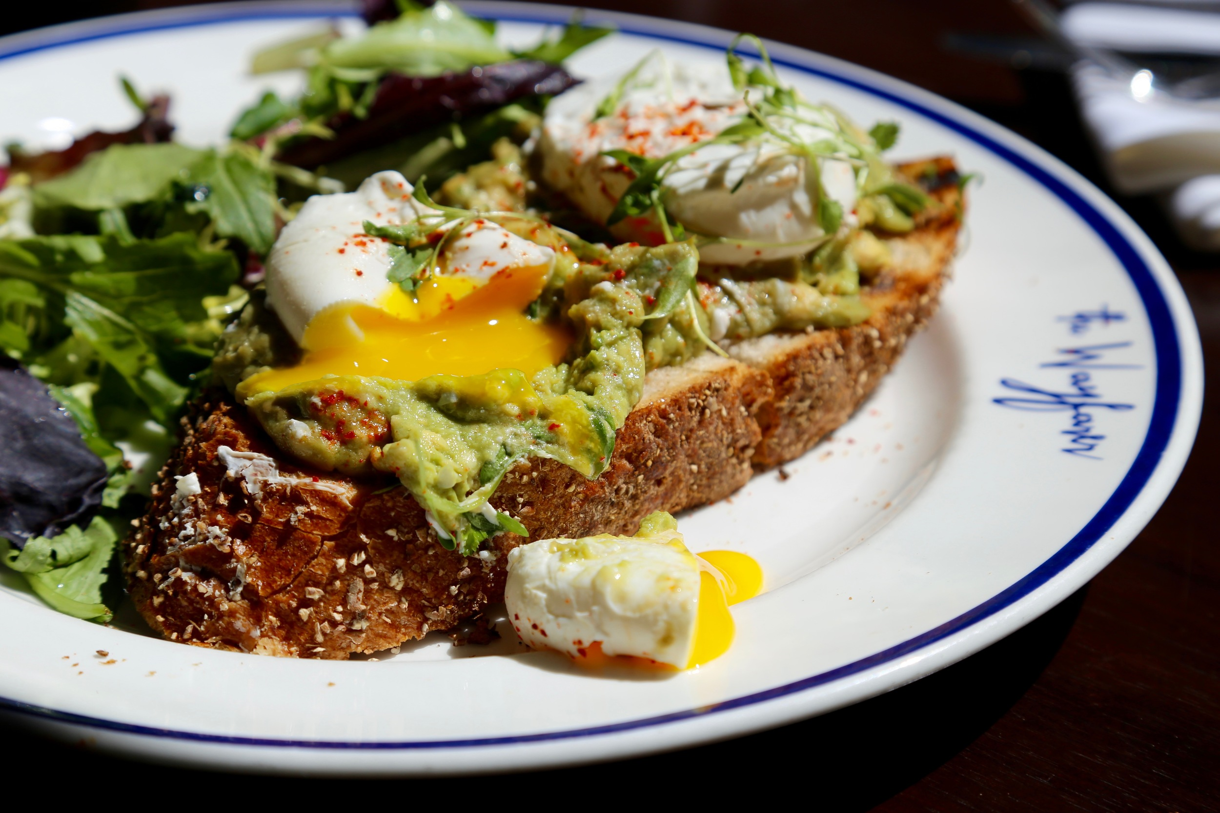 avocado toast with cracked open poached egg