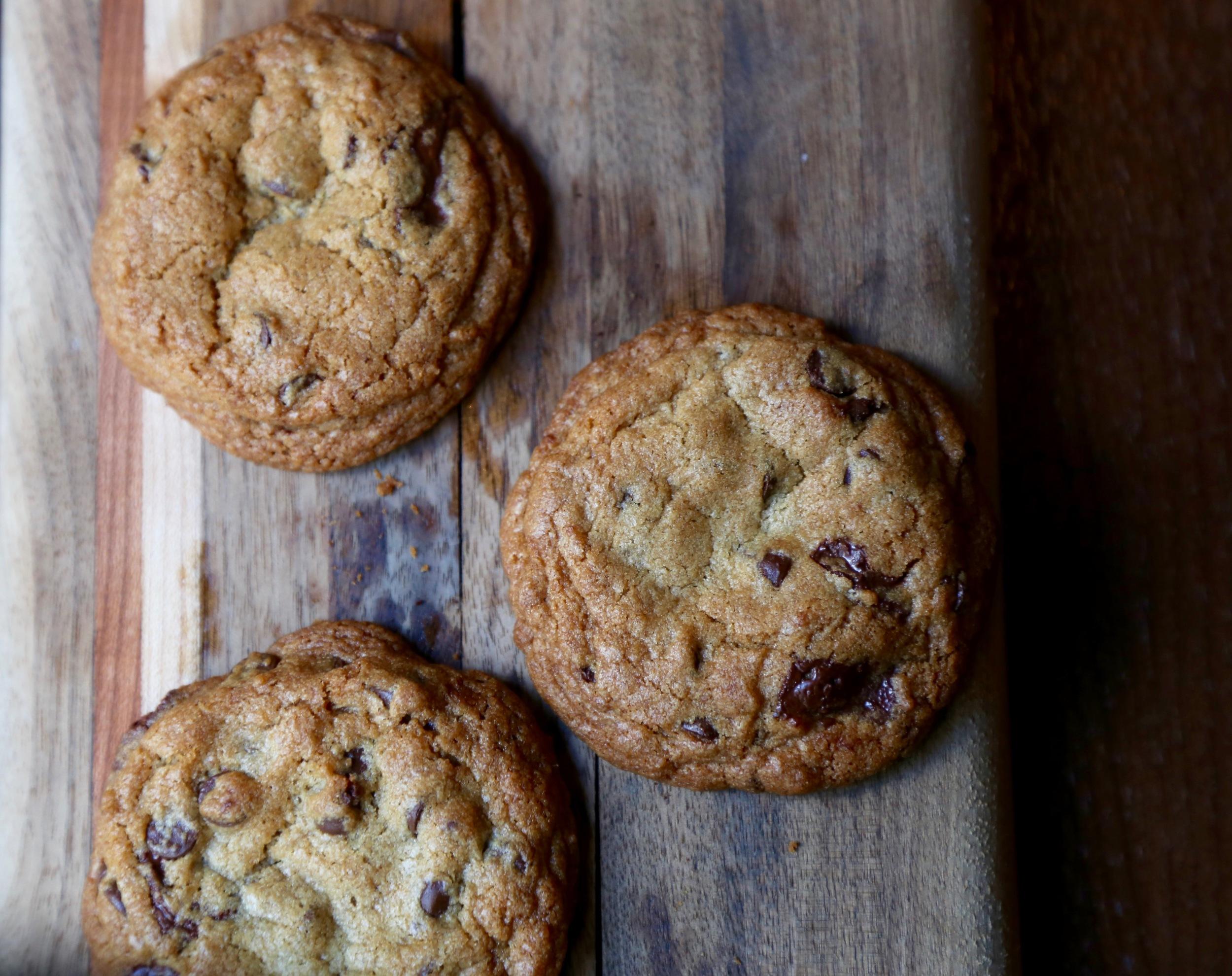 three chocolate chip cookies on wood table