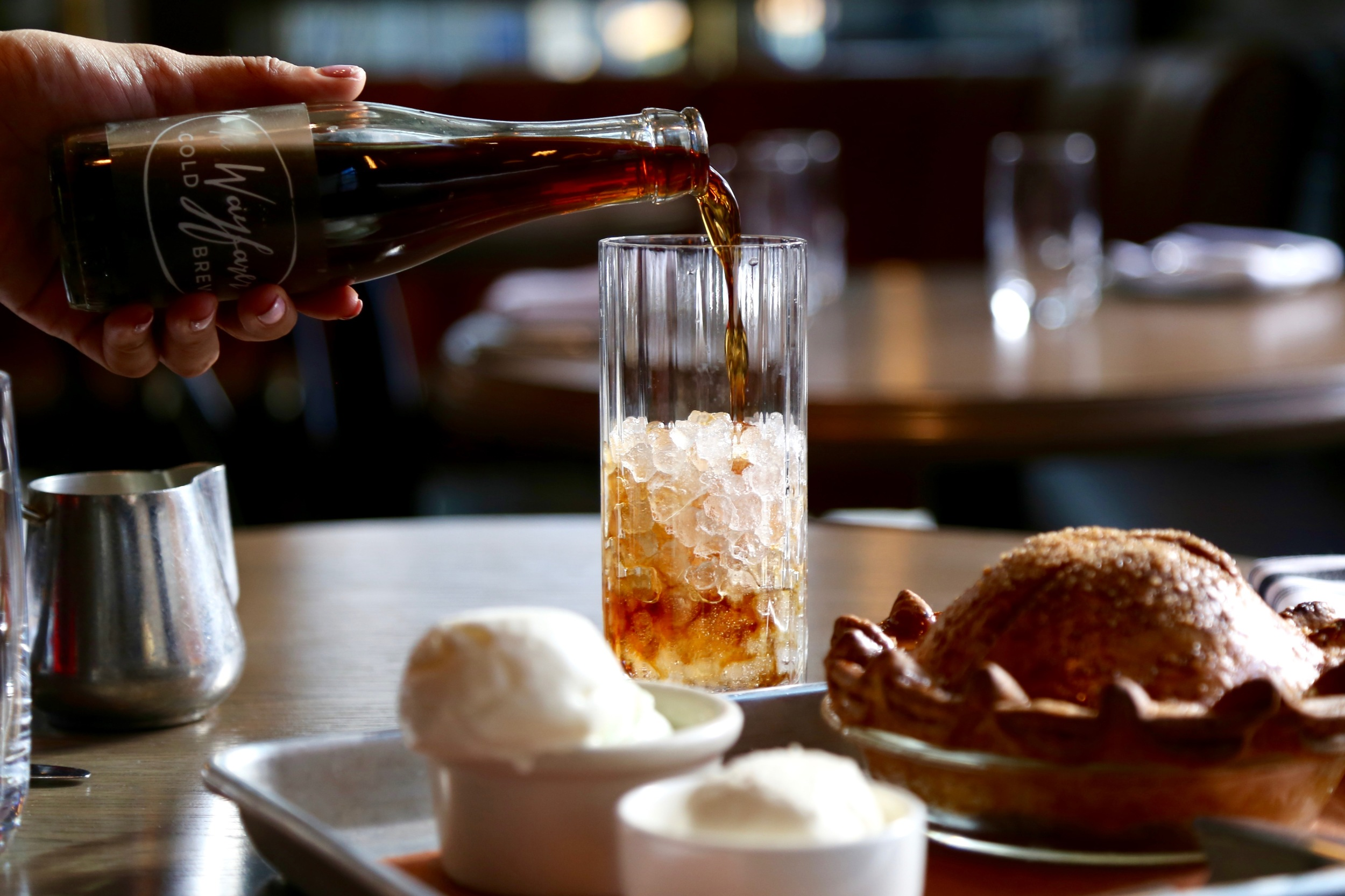 person pouring cold brew into cup filled with ice