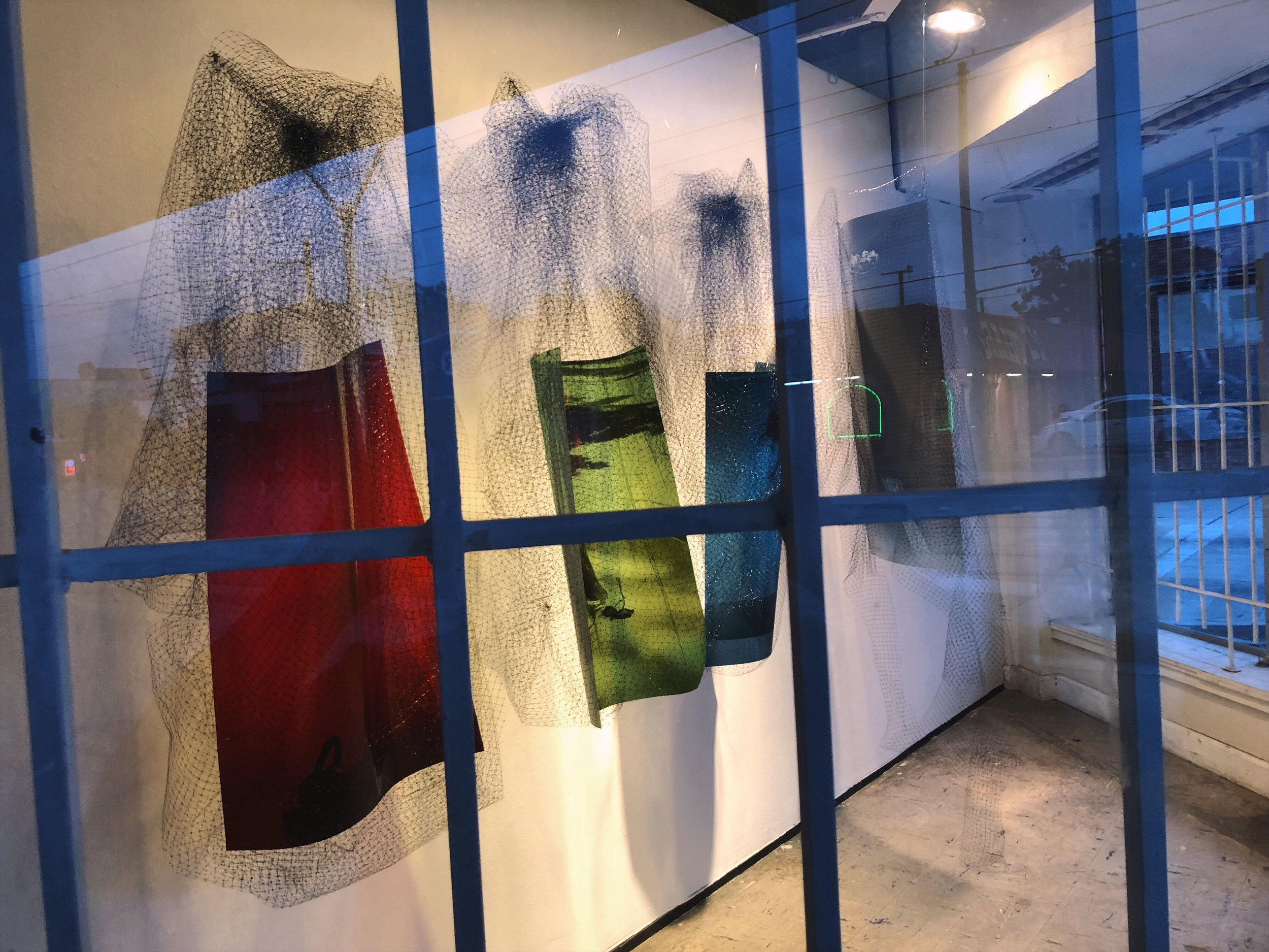 One view through the window. Each image is printed on transparency film, and suspended within bird block netting.  In the Window BOX viewers will experience Wallace's imaginings for potential solutions around thwarted self-preservation by using layers of photography, collage, objects, and texts that seek to suture the binaries.