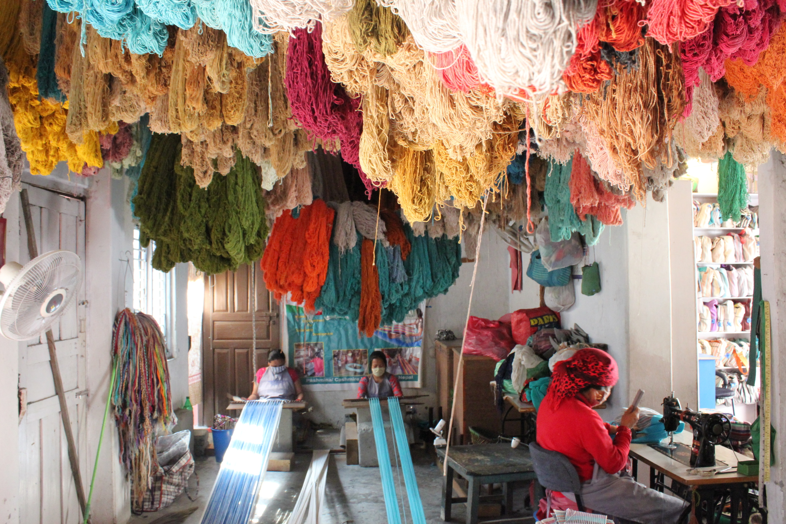 Hand dyed cotton hangs overhead as artisans from our partner Nepal Womens' Cooperative work on two back strap looms and a sowing machine.