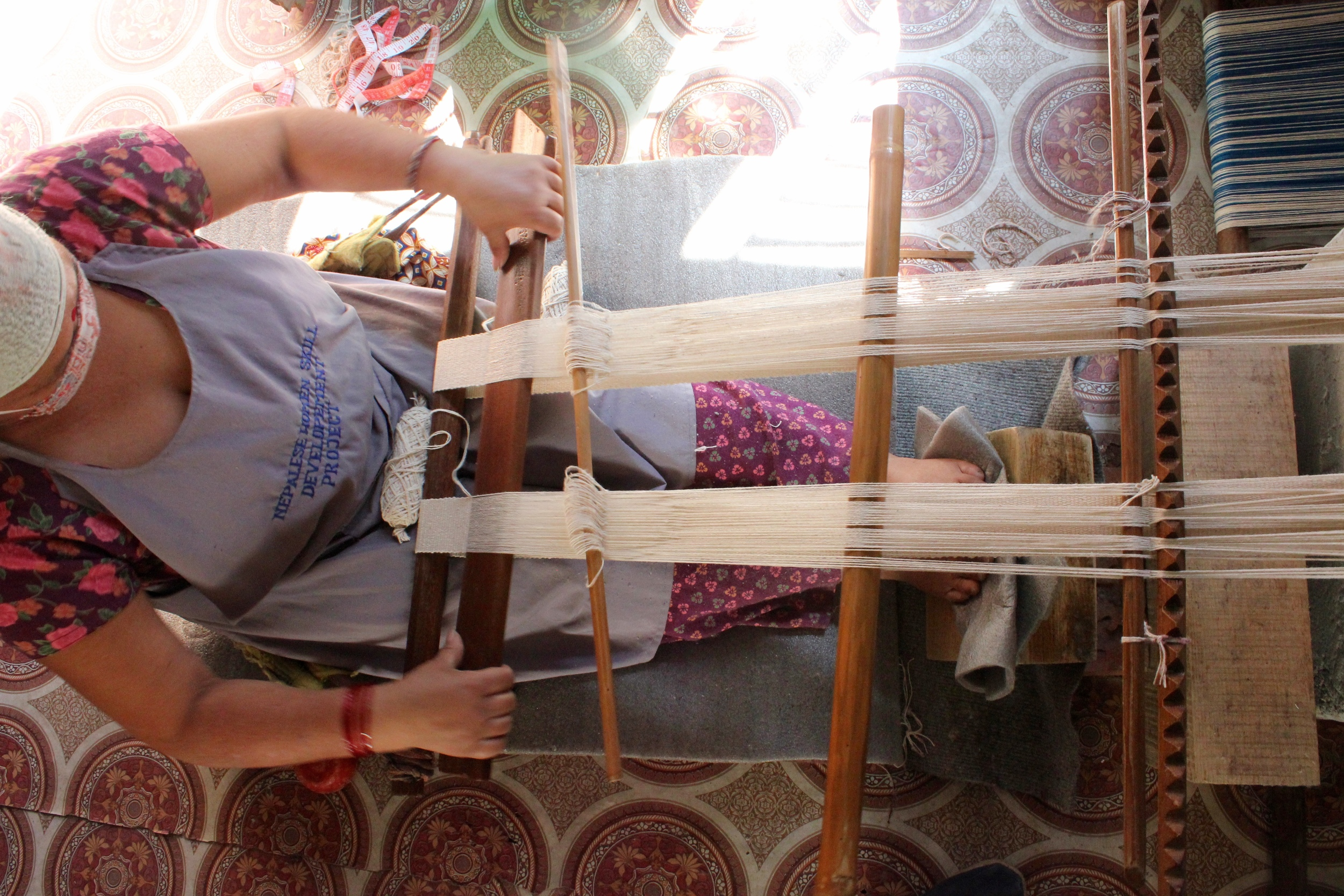 Yam Sari weaving on a traditional back strap loom in Nepal. It can take up to a week to create one table runner on a loom just like this one!