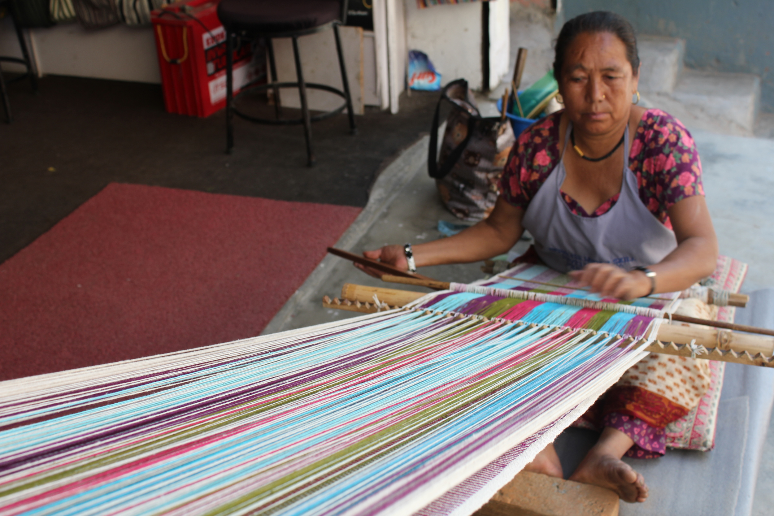 A traditional backs strap loom being used by Sita