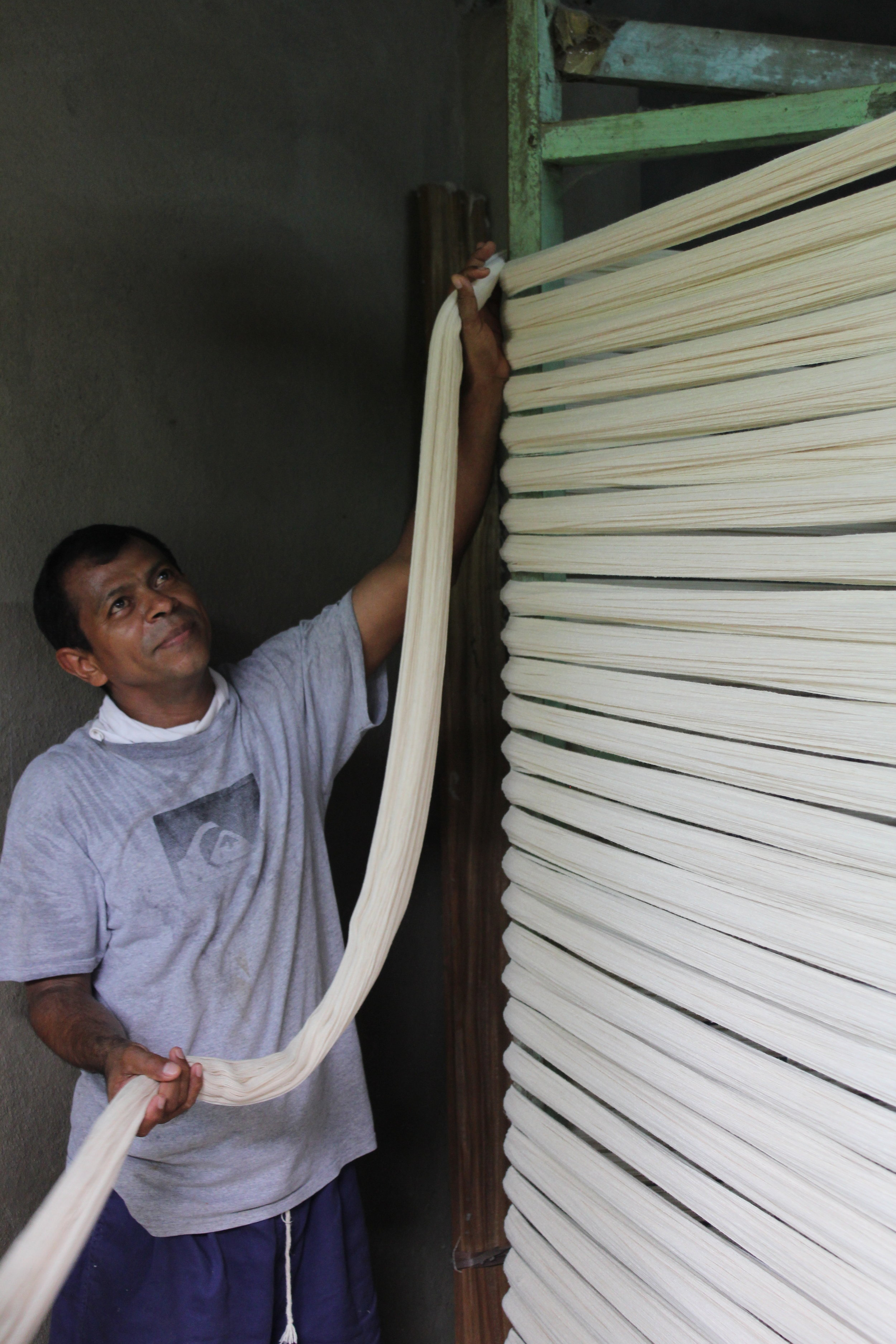 The natural fiber cotton is being prepared to set up on the loom by our artisan partner Huber in Nicaragua