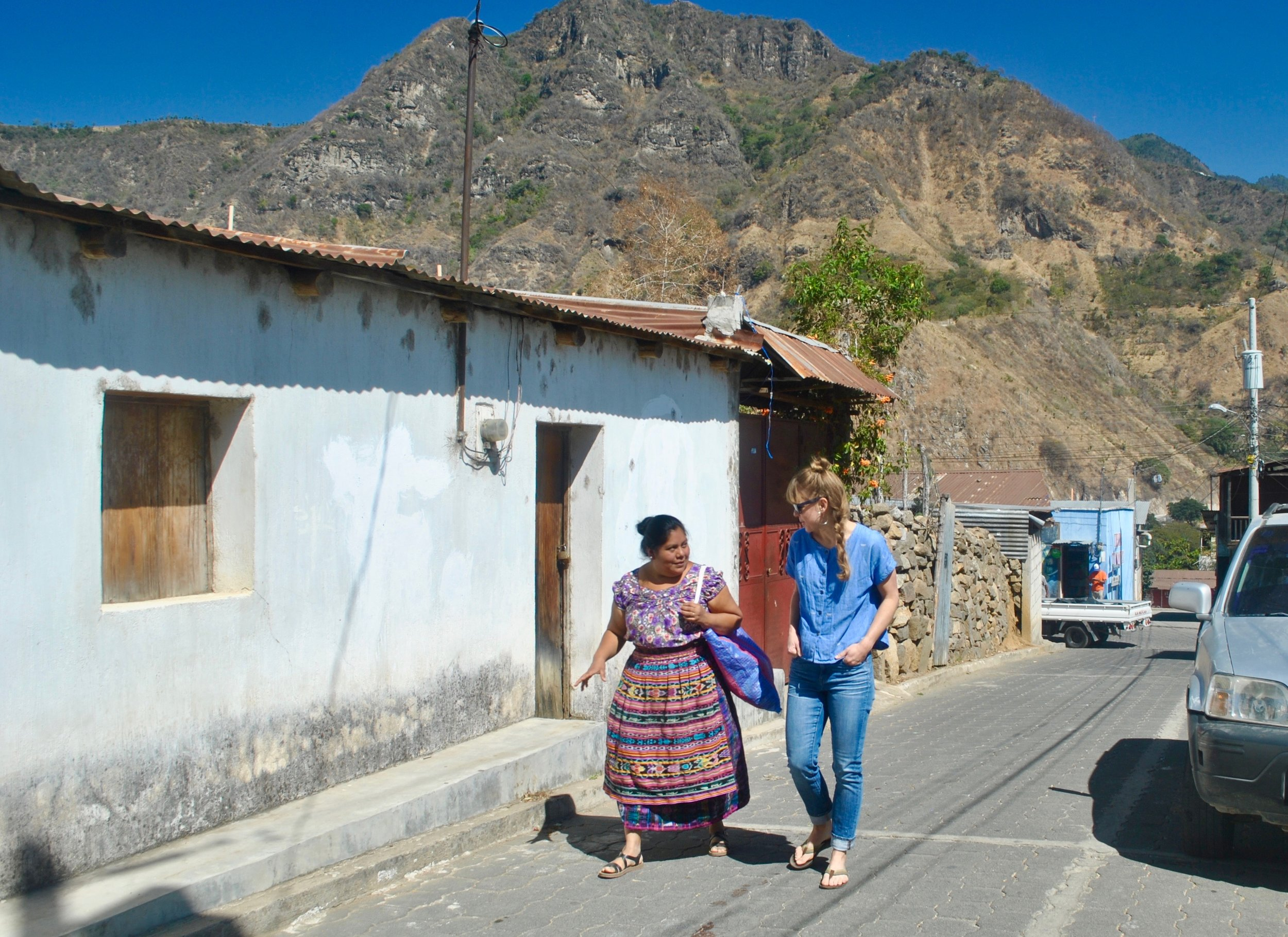 Amalia (President of our partner artisan cooperative in San Juan, Guatemala) walking with Amanda Zehner (Founder & CEO) to pick up products from one of our partner artisans.