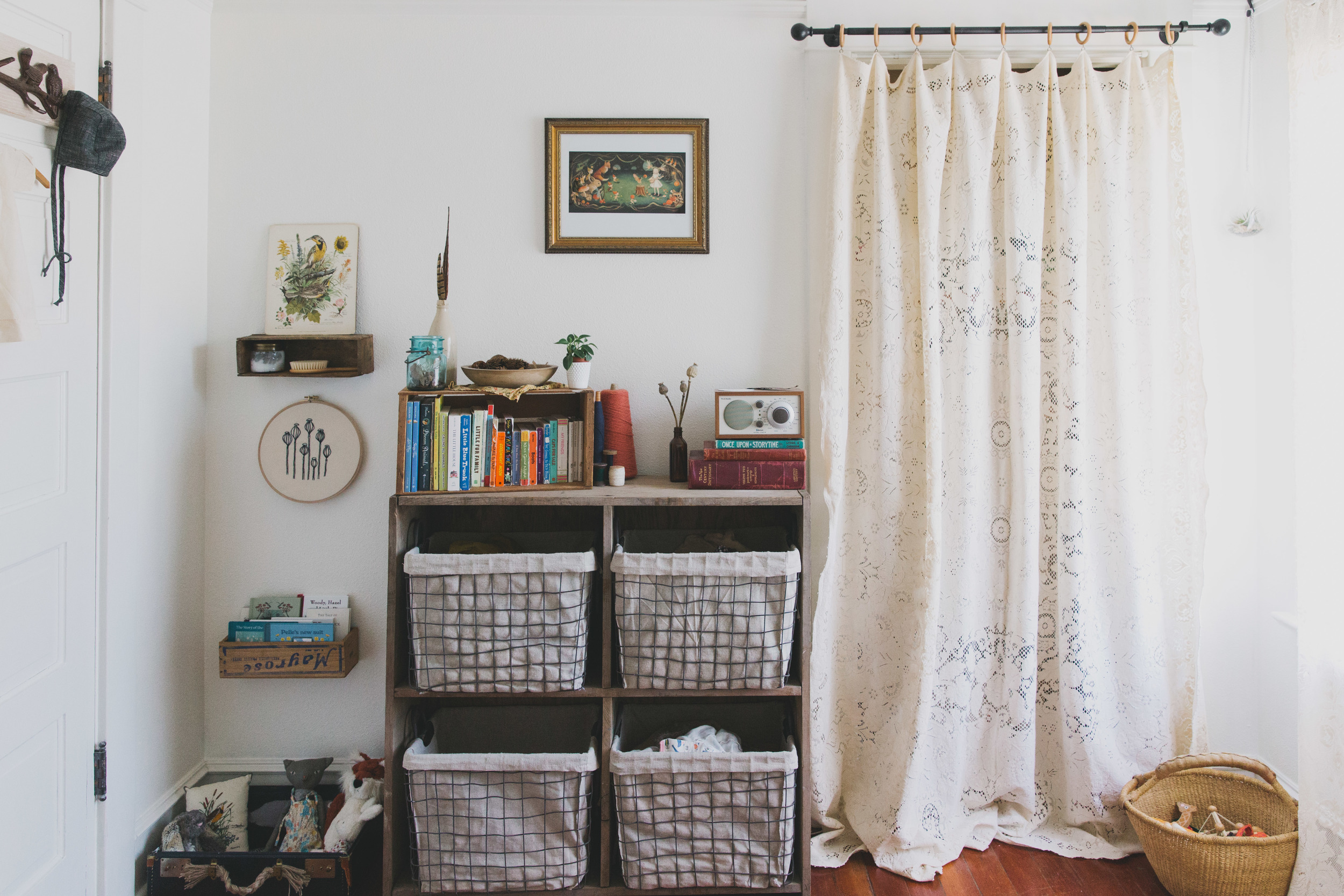 clothes, diaper supplies, & extra blankets are stored in the bins. i sewed wooden curtain rings to vintage lace tablecloths to make the closet and window curtains.