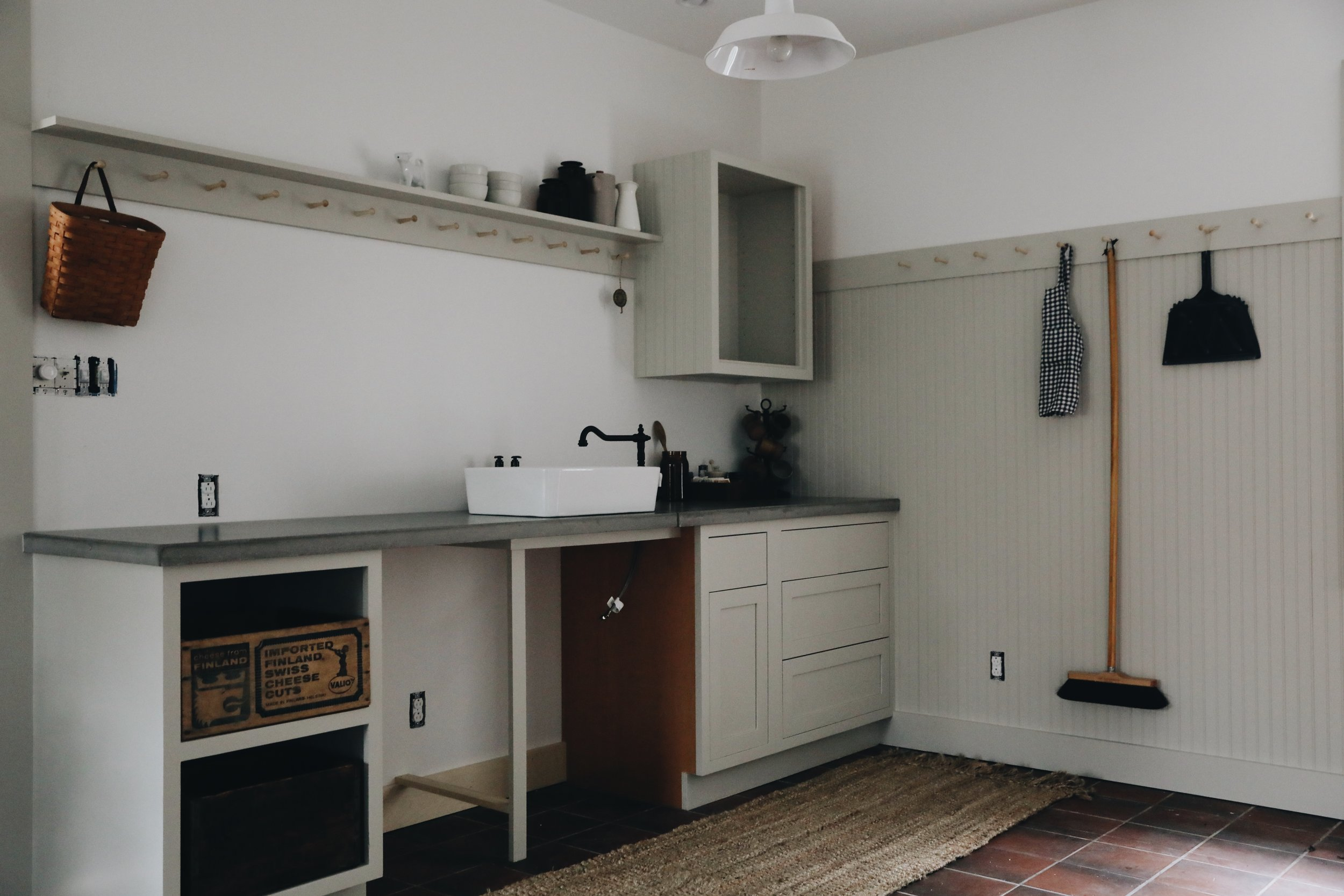 "our friend ben gilliom made the concrete countertops, which seemed like the most utilitarian option for a kids' craft space. paint color on cabinets and wainscoting is ""gatherings"" by magnolia."