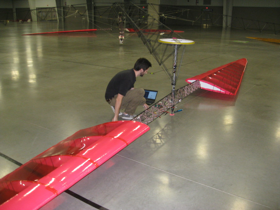 """Team member Ben Berry calibrates a strain gauge mounted on the rotor shaft (the rotor""""s truss spars are also visible)"""