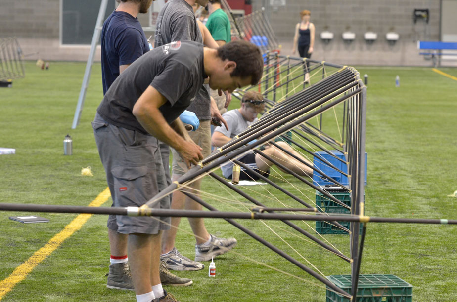 Aidan attaches the Vectran bracing lines to the top of one of the truss arms (photo credit Mike Campbell/ckmmphotgraphic)