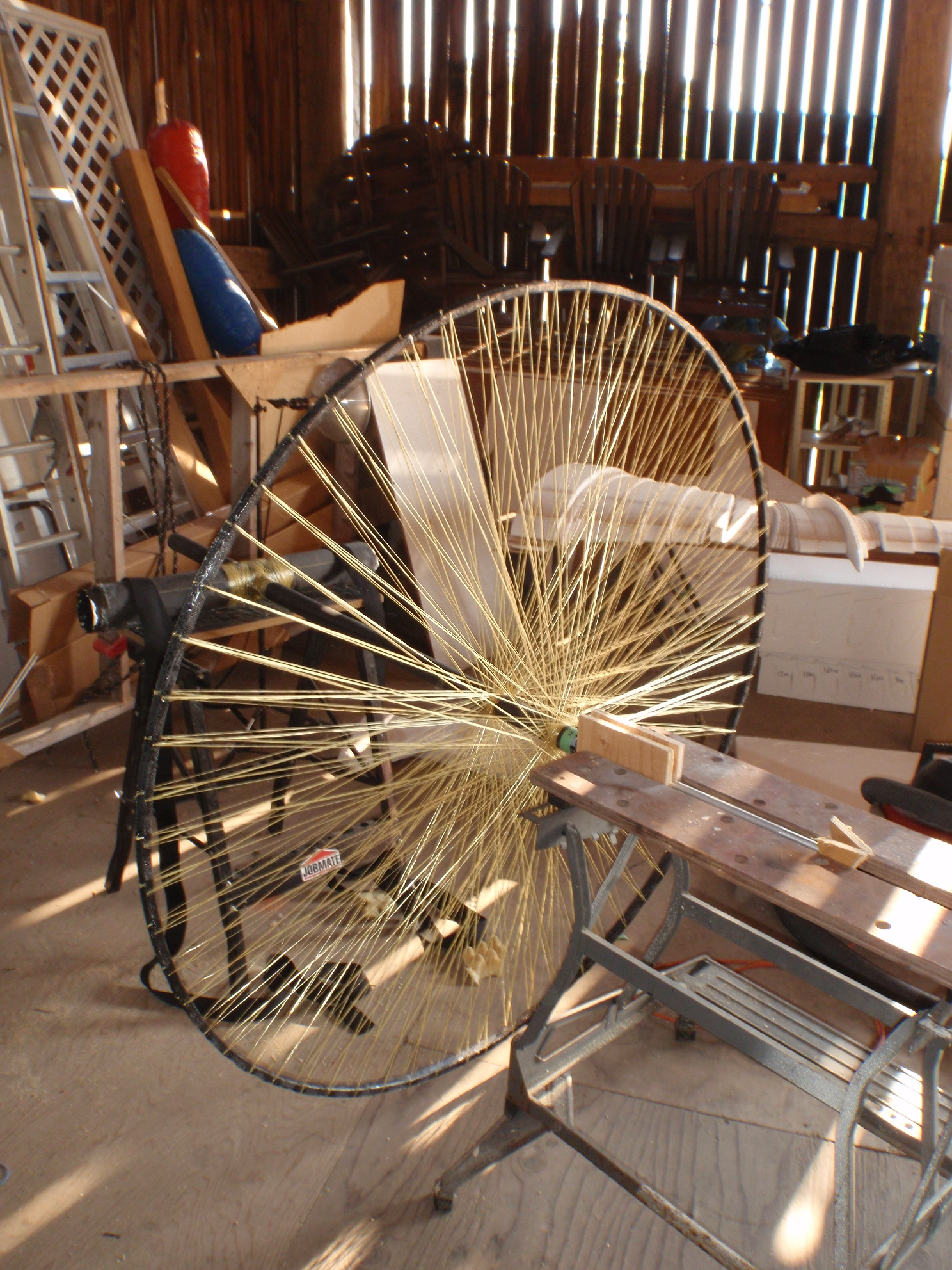 The drive spool has been mounted on a pair of saw horses for testing. The support near the spool is free to rotate, while the T-joint behind the spool is fixed in place.