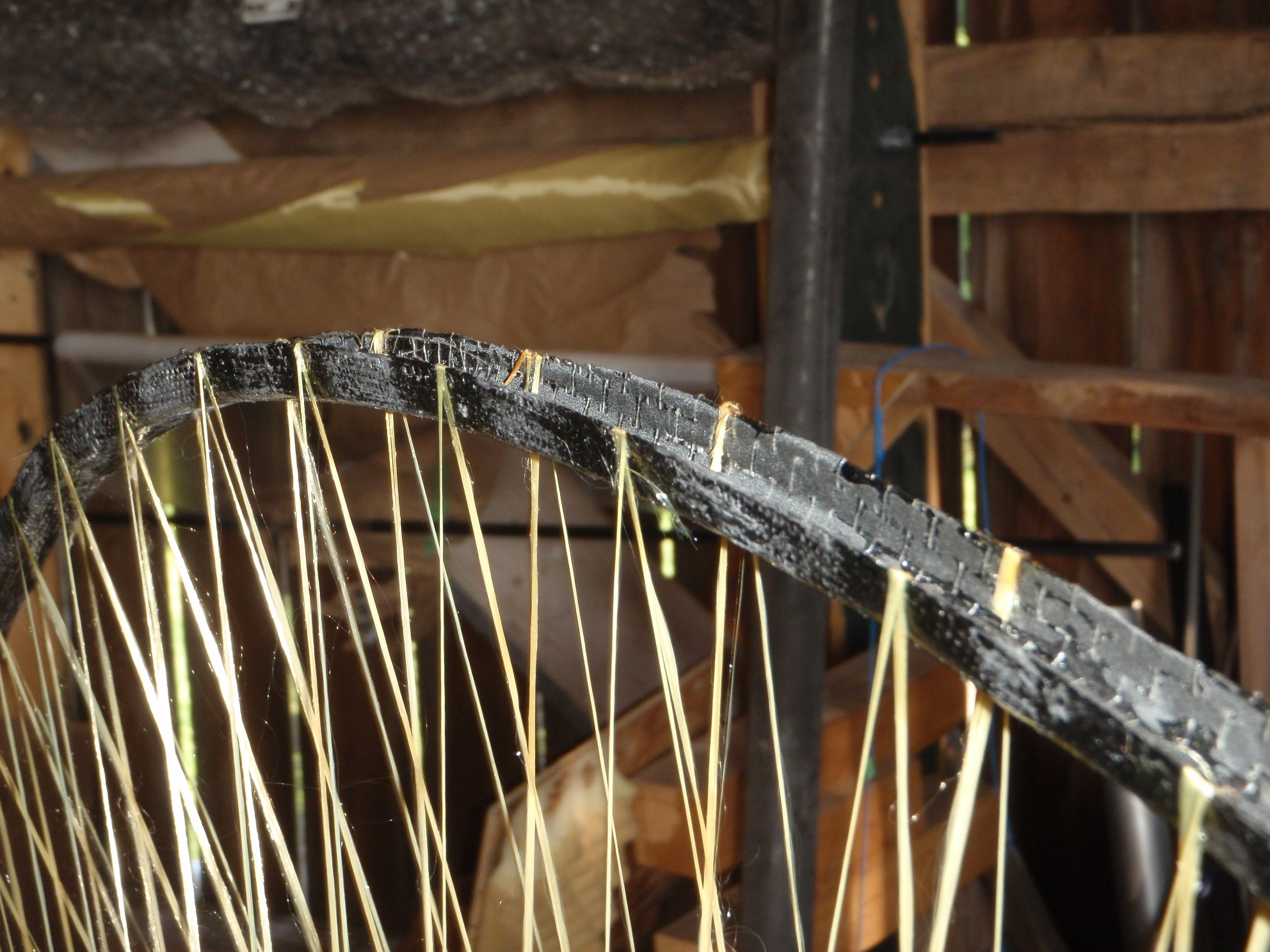 Shown is the rim of the completed spool. Note the crossover point of the original set of spokes. Also note the difference in the bond angle between the inner spokes and the outer spokes where they meet the rim.
