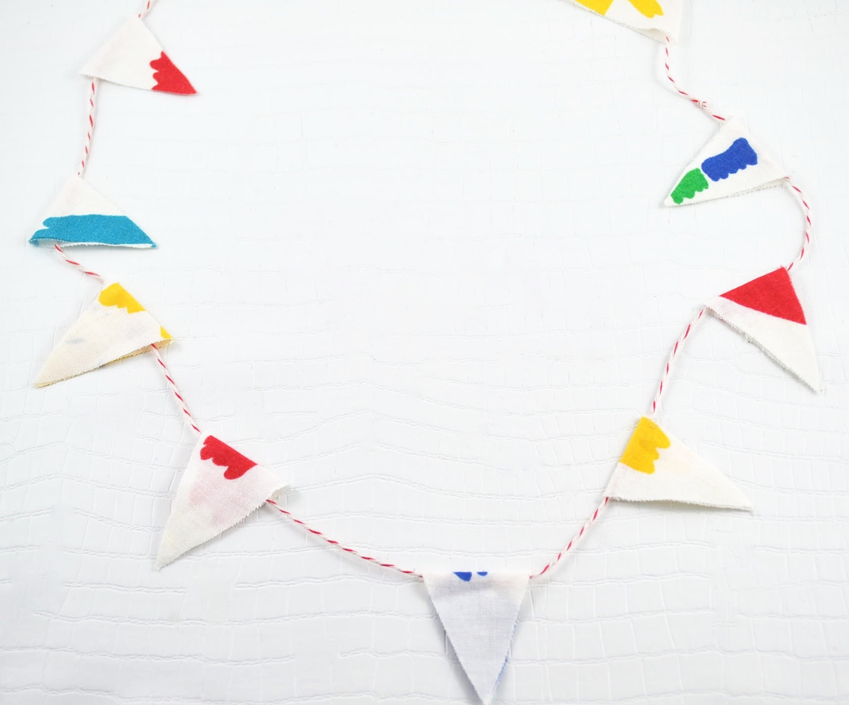 Homemade Bunting using material and gluing it closed with baker's twine. Photo Credit: Michelle Somers