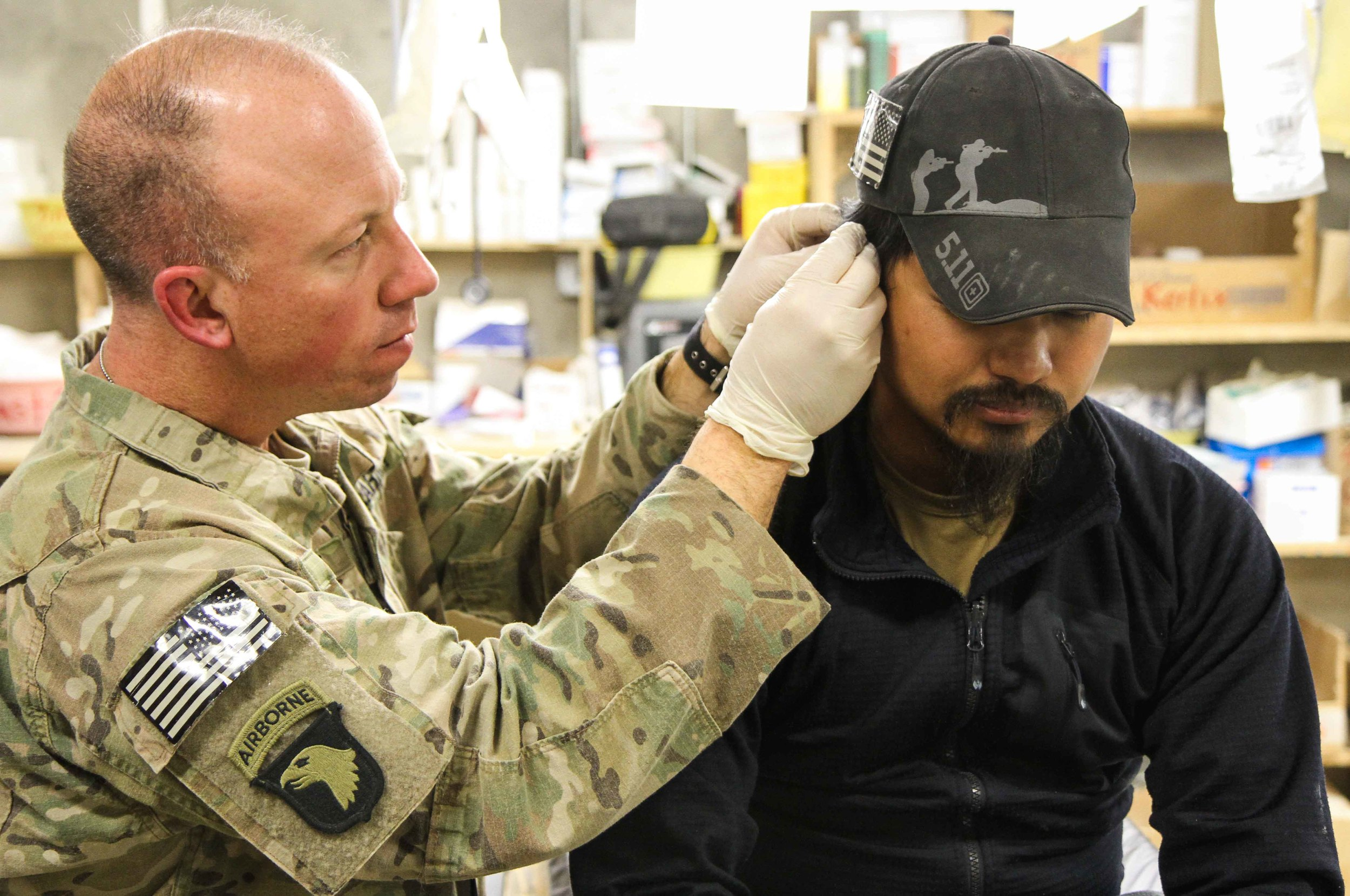 PAKTYA PROVINCE, Afghanistan - 1st Lt. Robert Blume inserts a thin gold needle through a U.S. civilian contractor's ear during a battlefield acupuncture session. (U.S. photo by Spc. Brian Smith-Dutton Task Force 3/101 Public Affairs)