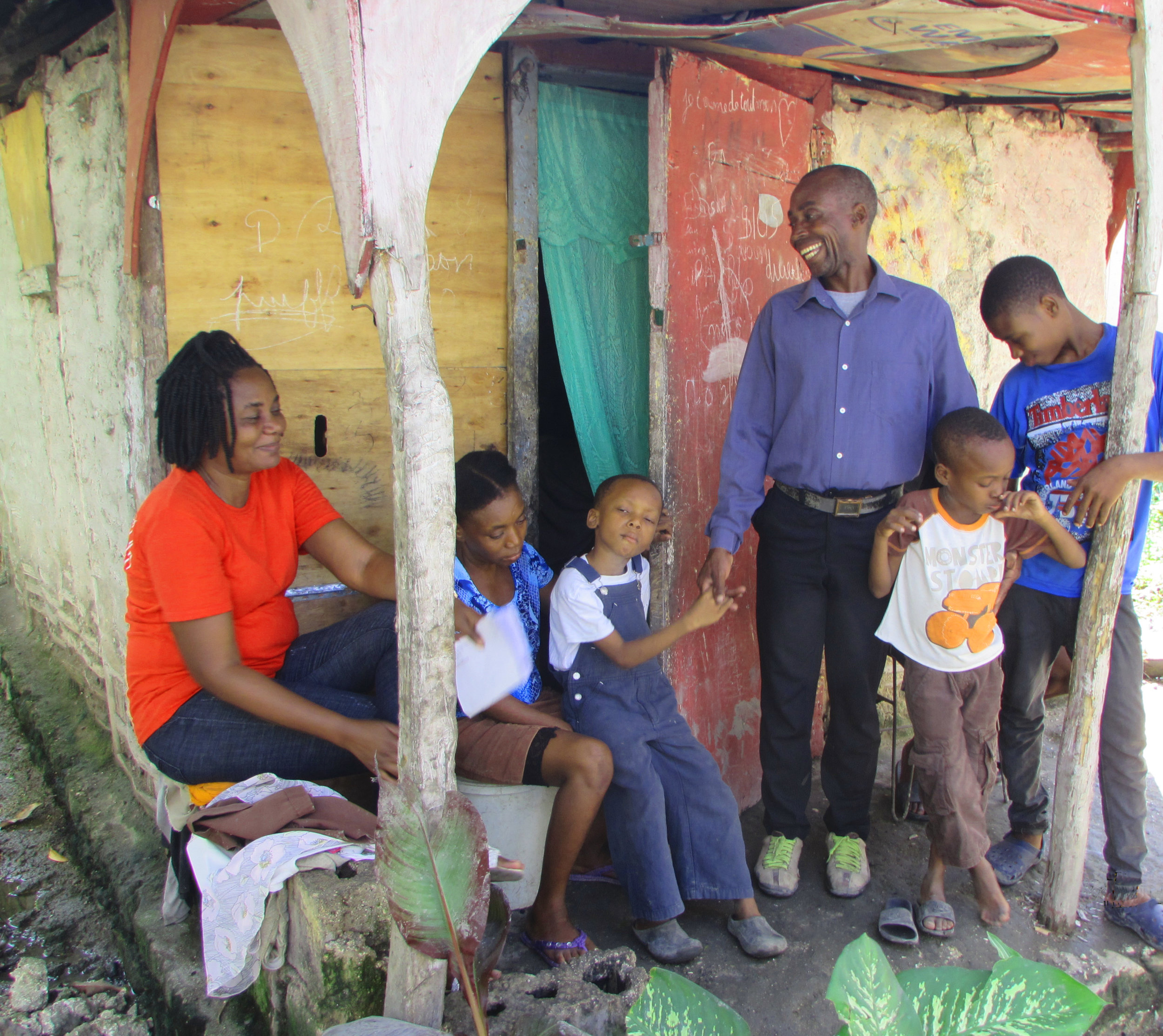 Kore Timoun Clinic Manager and  Monitrice  Guirlene Joseph (L) with Edouard Lape and family.