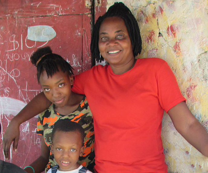 Old friends Patricia Lapé (L) and Guirlene Joseph, with Patricia's little brother.