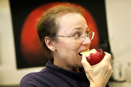 Scientist Kate Evans takes a bite of a Cosmic Crisp.